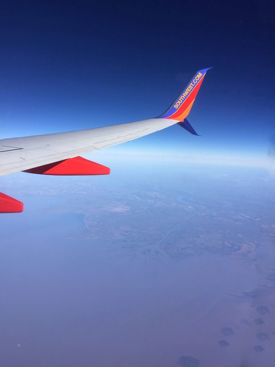 airplane, transportation, flying, aerial view, sky, airplane wing, no people, blue, aircraft wing, air vehicle, nature, outdoors, day, mid-air, journey, red, beauty in nature, scenics