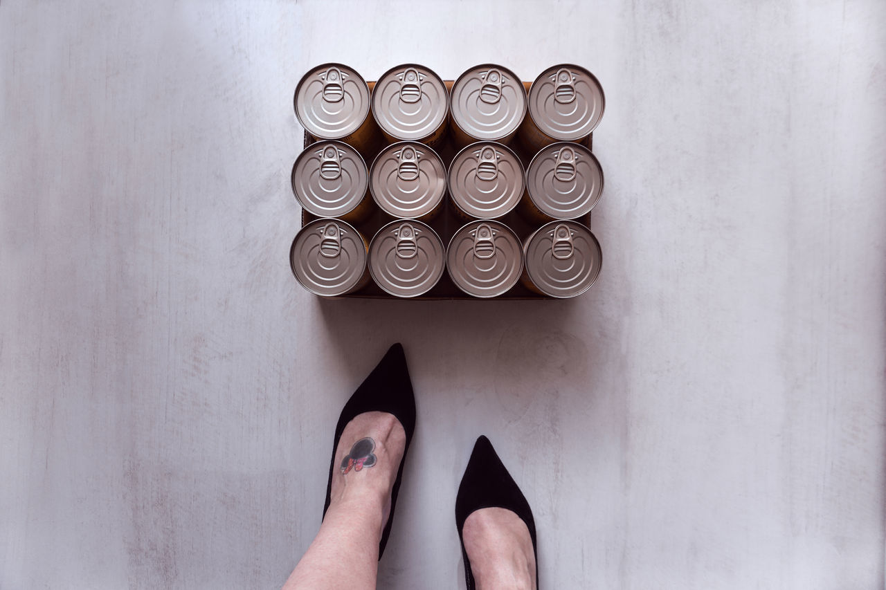 Low Section Of Woman Standing By Tin Cans