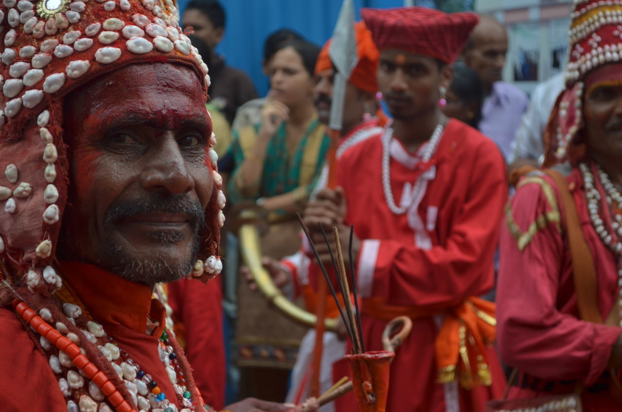 real people, red, focus on foreground, tradition, traditional clothing, cultures, celebration, parade, day, performance, event, men, togetherness, outdoors, music, playing, large group of people, musician