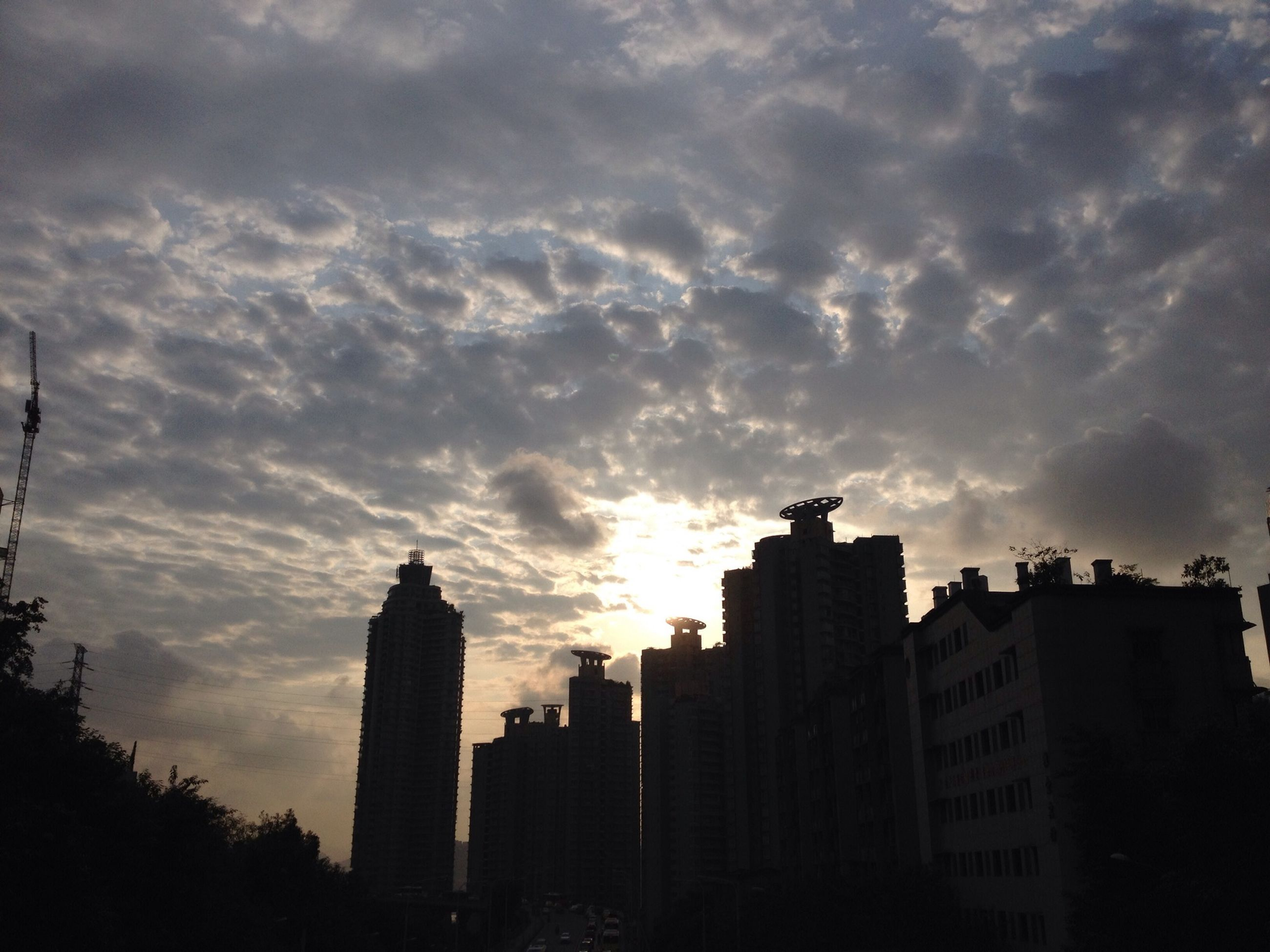 building exterior, architecture, built structure, sky, city, silhouette, sunset, cloud - sky, cloudy, low angle view, building, cloud, skyscraper, dusk, cityscape, city life, outdoors, overcast, residential building, tower
