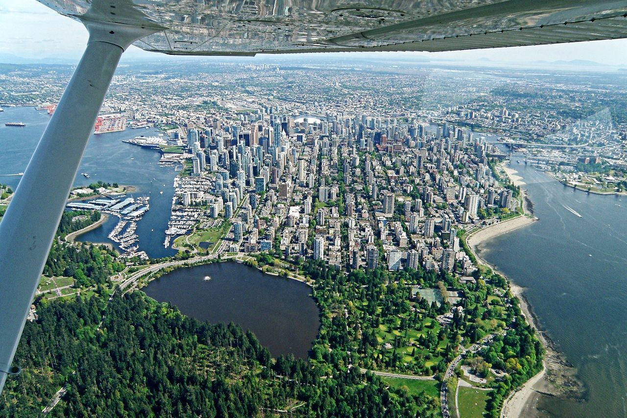 aerial view, water, transportation, cityscape, architecture, high angle view, day, city, built structure, no people, outdoors, airplane, building exterior, river, flying, air vehicle, landscape, nature, sky, airplane wing