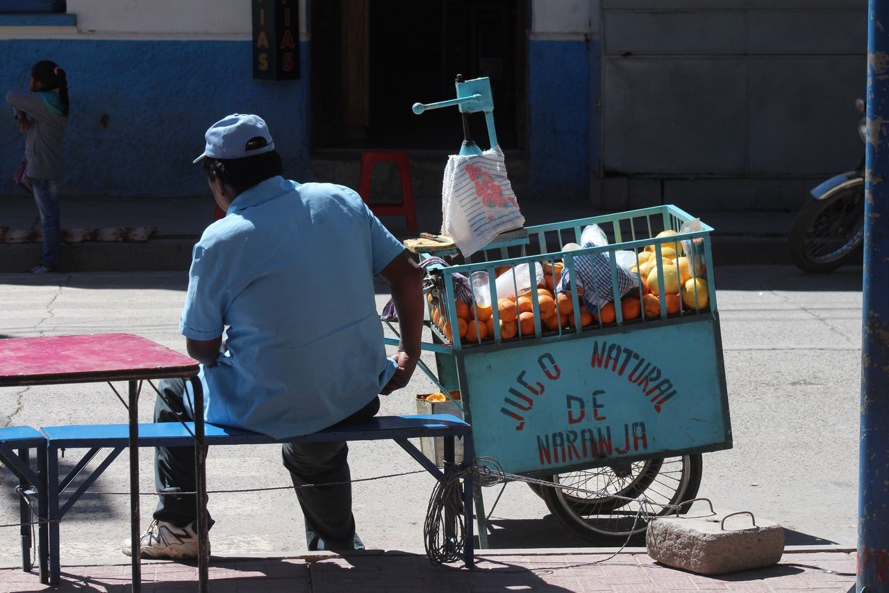 Tranquilo tranquilo fresh orange juice in Bolivia. Bolivia Streetphotography Welcomeweekly Sunlight Street Photography South America Sitting Lifestyles TUPIZA Food Real People Men One Person Outdoors Market One Man Only Day People