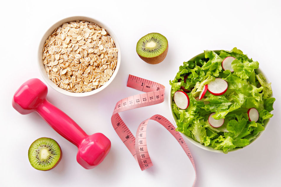 Flat lay diet concept. Top view of tape measure, kiwi fruit, pink weight, salad and oat flakes. Healthy and fresh breakfast on white background Balance Bowl Close-up Concept Dieting Eating Food Freshness Fruit Green Color Healthy Eating Healthy Lifestyle High Angle View Kiwi Lettuce Loss No People Oats Organic Radish Salad Slim Tape Measure Weightloss Weights