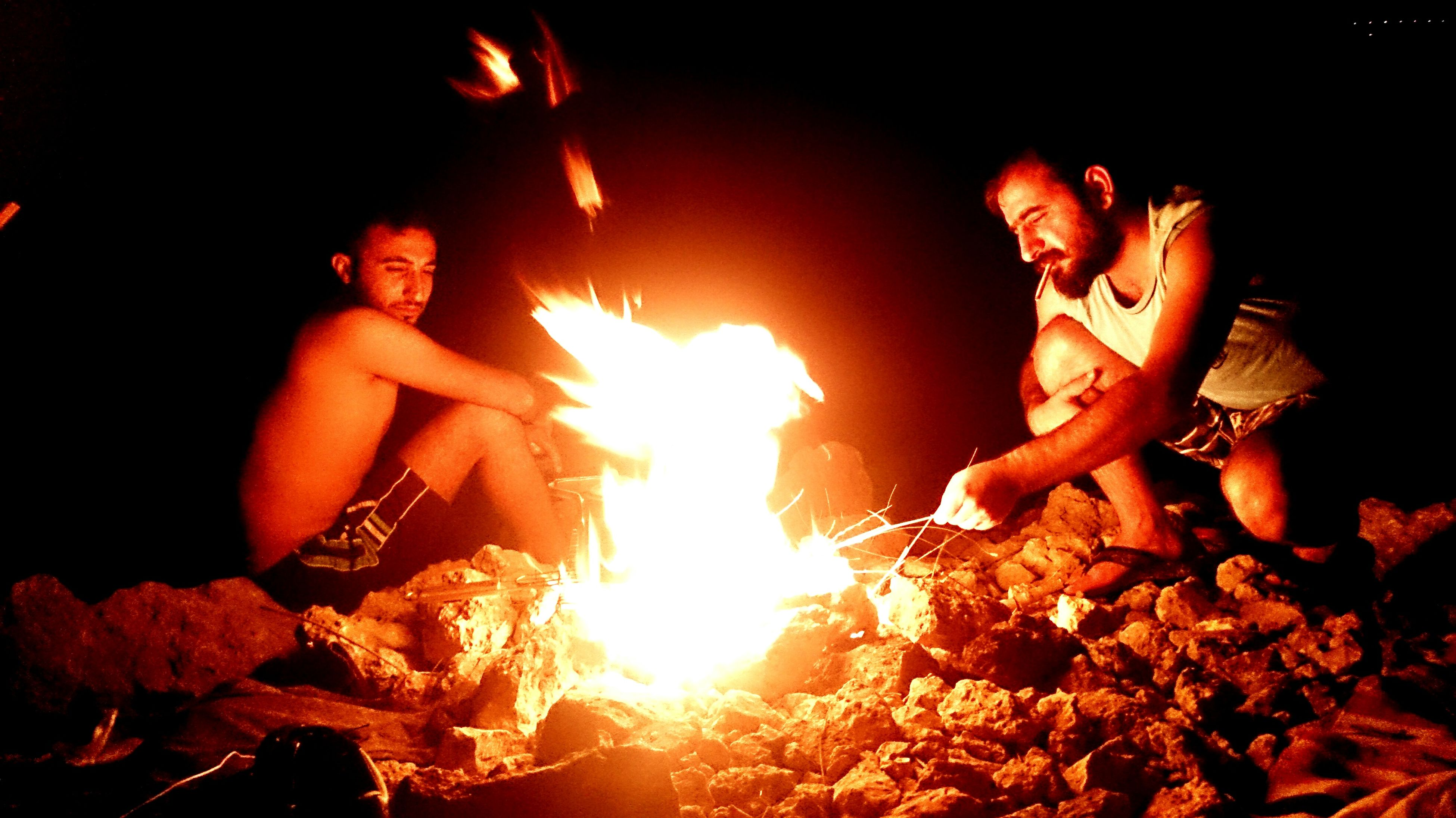 burning, night, flame, fire - natural phenomenon, heat - temperature, glowing, orange color, fire, bonfire, lifestyles, leisure activity, holding, illuminated, outdoors, standing, dark, campfire, person