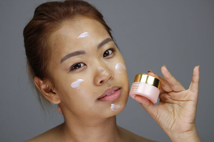 Adult Adults Only Beautiful Woman Beauty Beauty Spa Beauty Treatment Body Care Bottle Close-up Day Gray Background Headshot Holding Indoors  Looking At Camera Moisturizer One Person One Young Woman Only People Portrait Studio Shot Young Adult Young Women