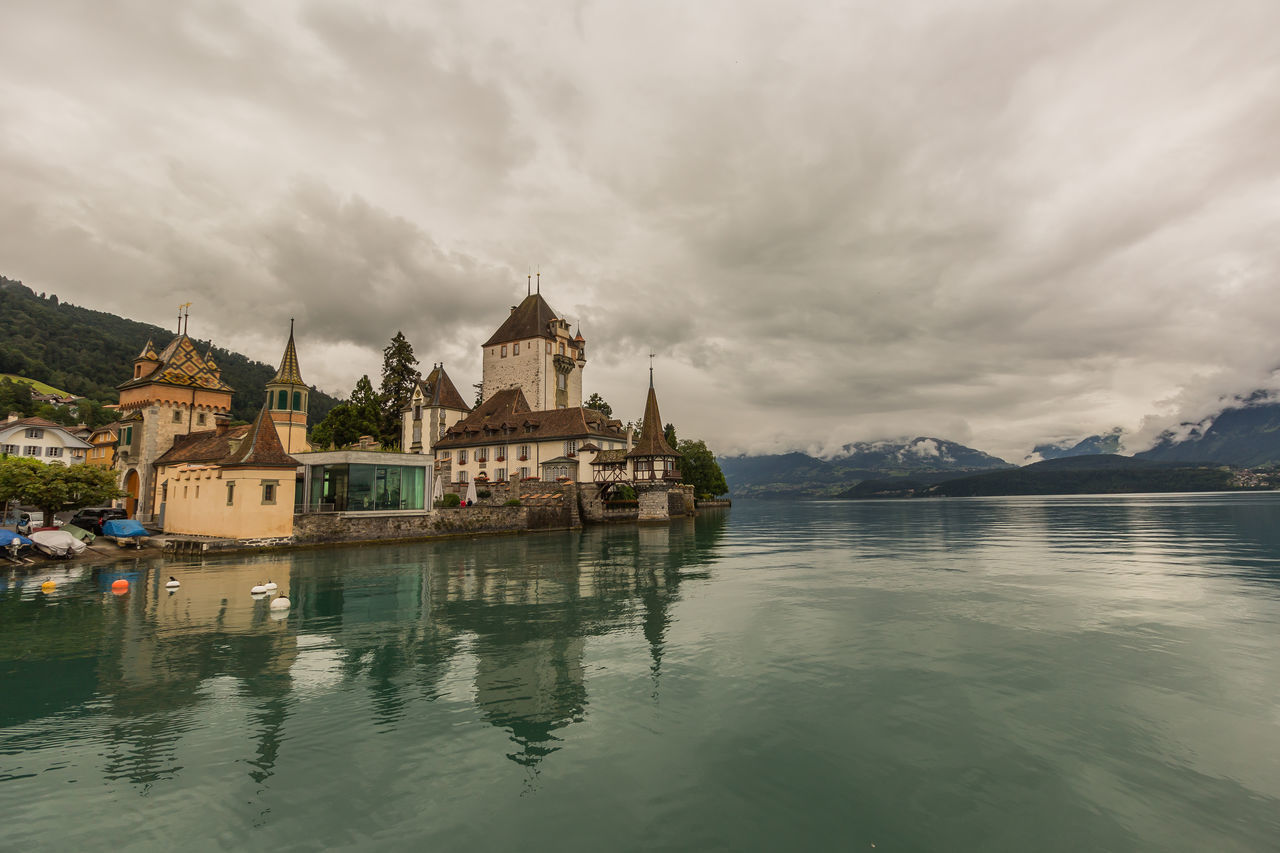 Schloss Oberhofen, Switzerland Architecture Built Structure Canal Castle Castles Cloud Cloud - Sky Cloudy Day Mountain Nature No People Outdoors Overcast Rippled Scenics Schloss Oberhofen Sky Tranquility Travel Destinations Water Waterfront Weather