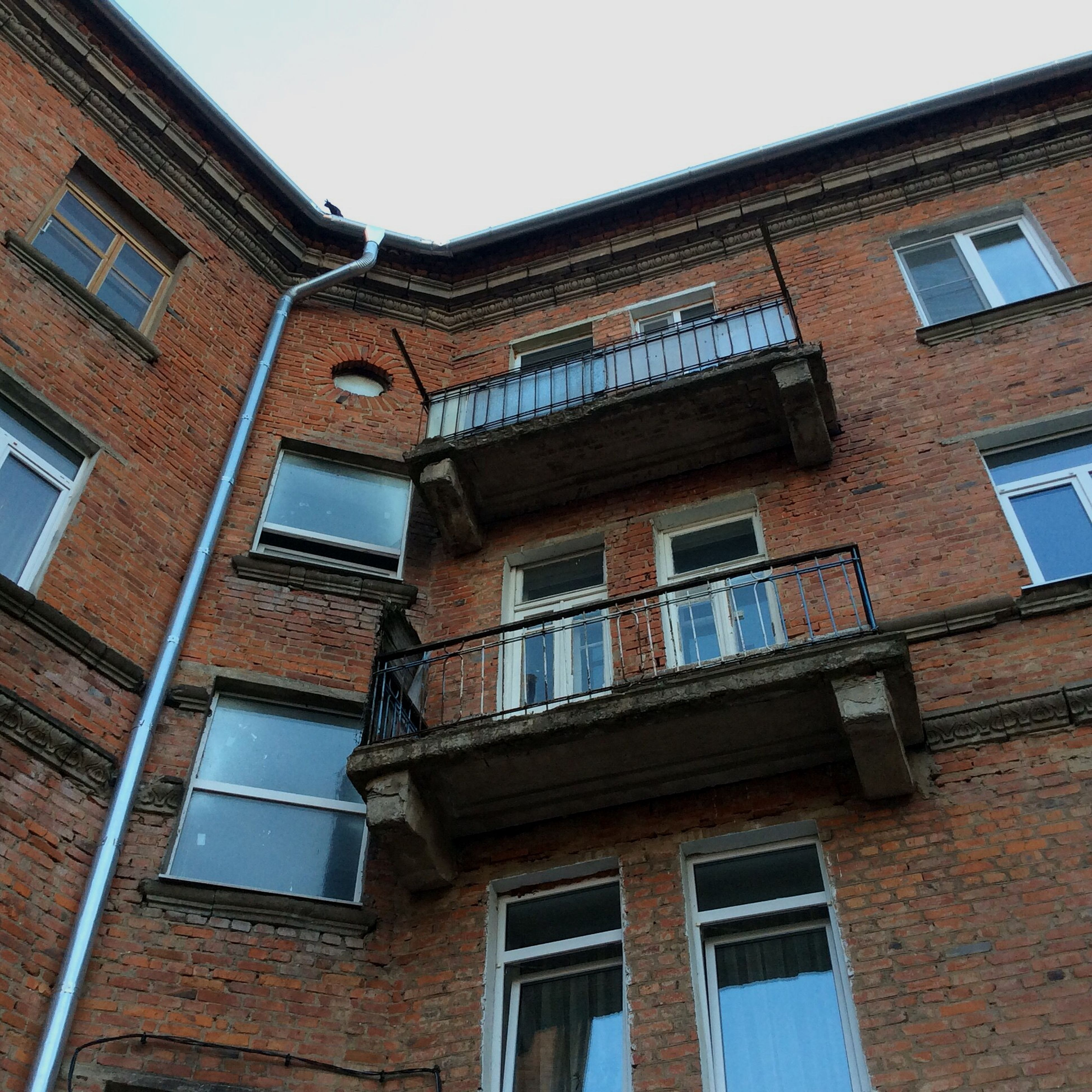 architecture, building exterior, built structure, window, low angle view, residential building, residential structure, building, house, clear sky, balcony, day, brick wall, apartment, outdoors, no people, sky, city, old, facade