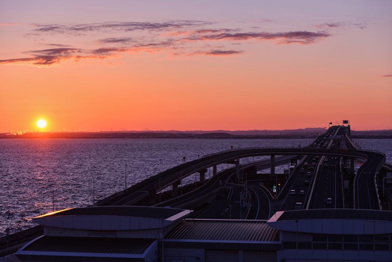 Bridge across sea at sunset