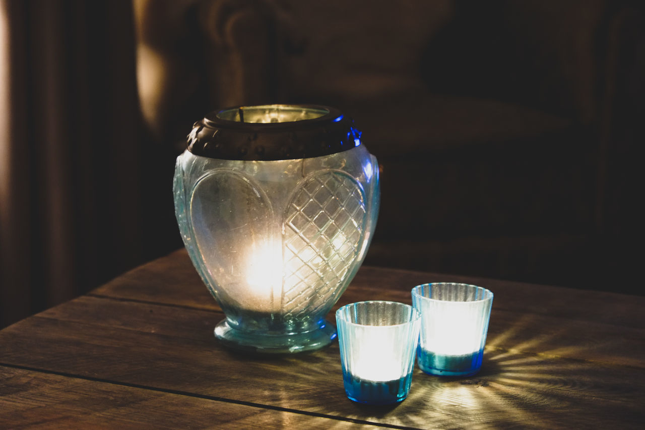 table, no people, indoors, drinking glass, focus on foreground, close-up, burning, illuminated, flame, drink, night