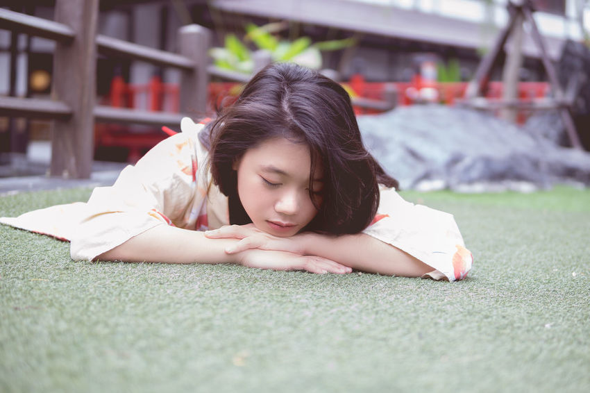 Beautiful Woman Childhood Close-up Day Grass Lawn Leisure Activity Lifestyles Lying Down Lying On Front One Person Outdoors People Real People Relaxation Sitting Young Adult Young Women