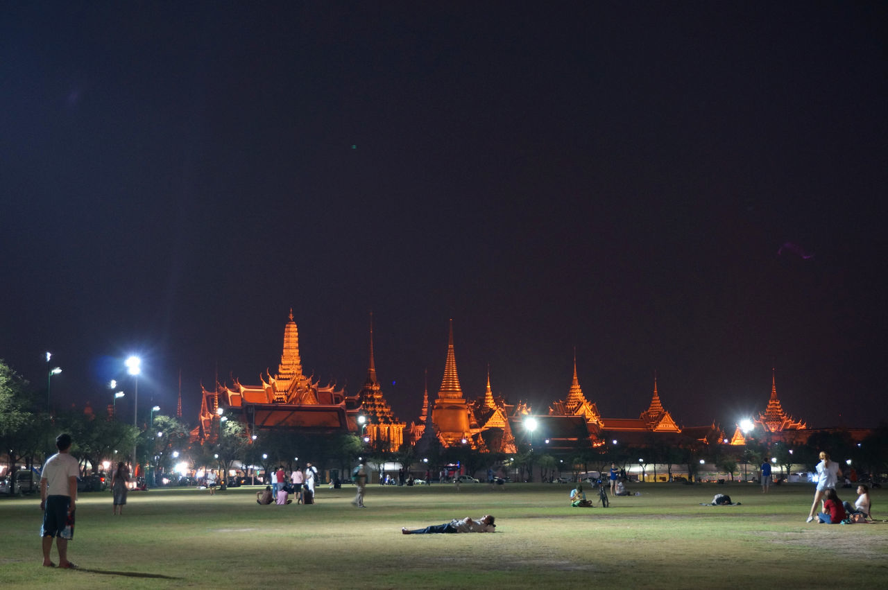 Thai people relax in the Royal field near The Emerald Buddha temple Ancient Architecture Bangkok Cultures Famous Place History Place Of Worship Real People Religion Spirituality Temple Temple - Building Thailand Spotted In Thailand