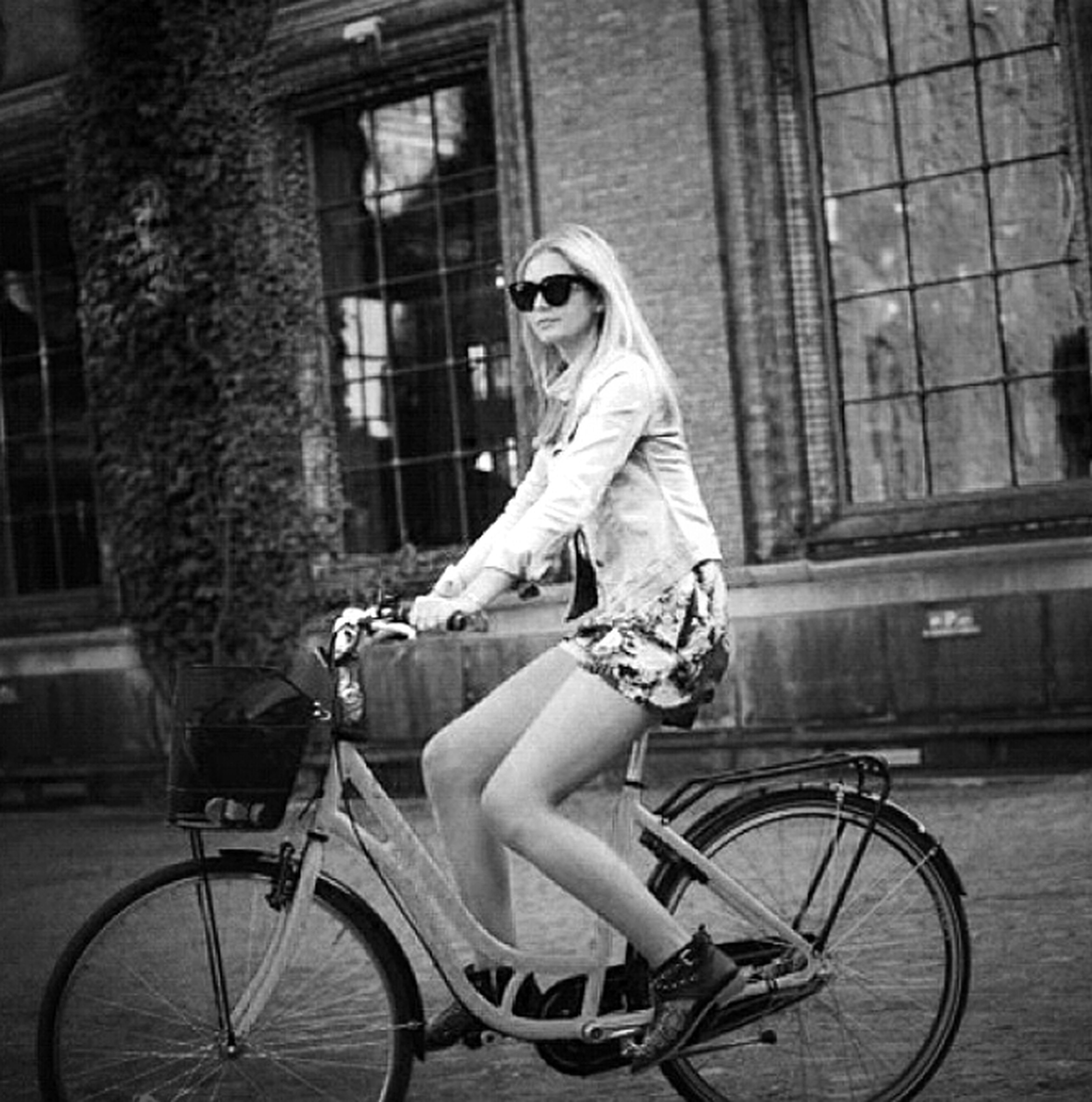 bicycle, mode of transport, building exterior, land vehicle, transportation, architecture, built structure, full length, lifestyles, side view, casual clothing, leisure activity, young adult, riding, sitting, window, street, city
