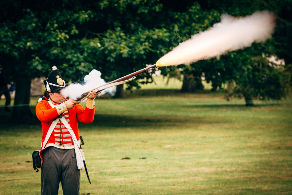 Adult Day Fire Grass Gun Historical Reenactment Motion Nature Old One Man Only One Person Outdoors Real People Red Rifle Shoting Smoke Tree War