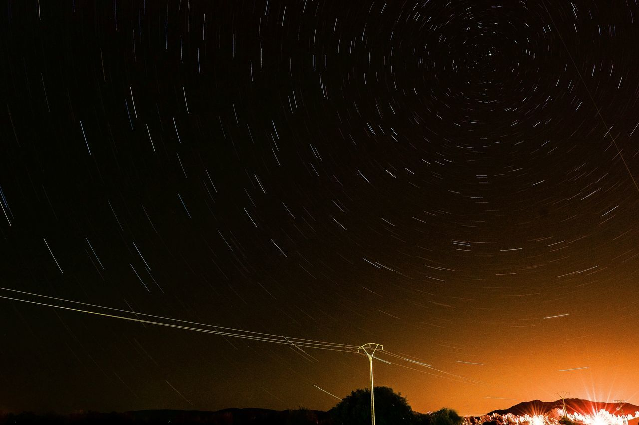 night, nature, scenics, beauty in nature, outdoors, low angle view, star trail, no people, star - space, tranquil scene, cable, sky, astronomy, tranquility, moon, technology, mountain, galaxy, industrial windmill