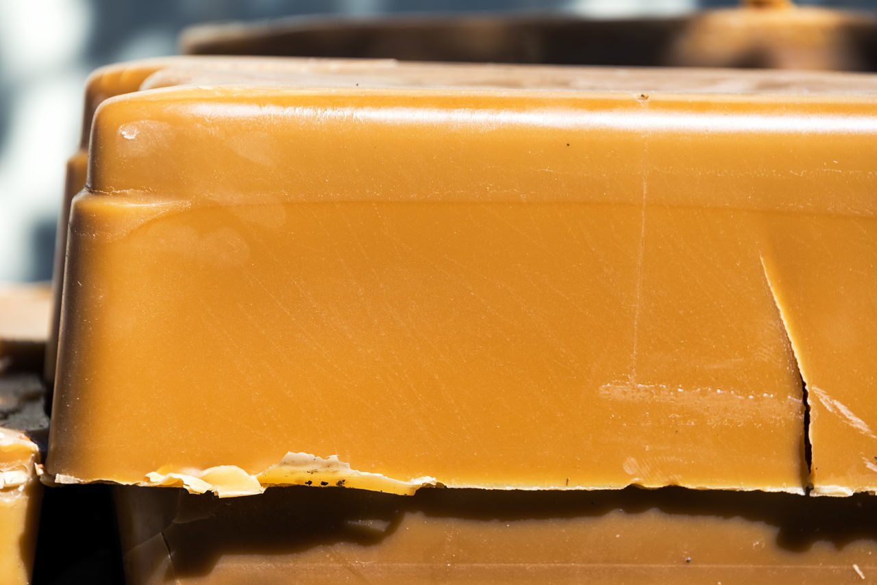 Closeup view of a brick of beeswax in Buffalo, Wyoming Agriculture Apiary Bee Beehive Beehives Beekeeping Bees Beeswax Buffalo Day Freshness Honey Honeycomb No People Orange Organic Outdoors Wax Wyoming