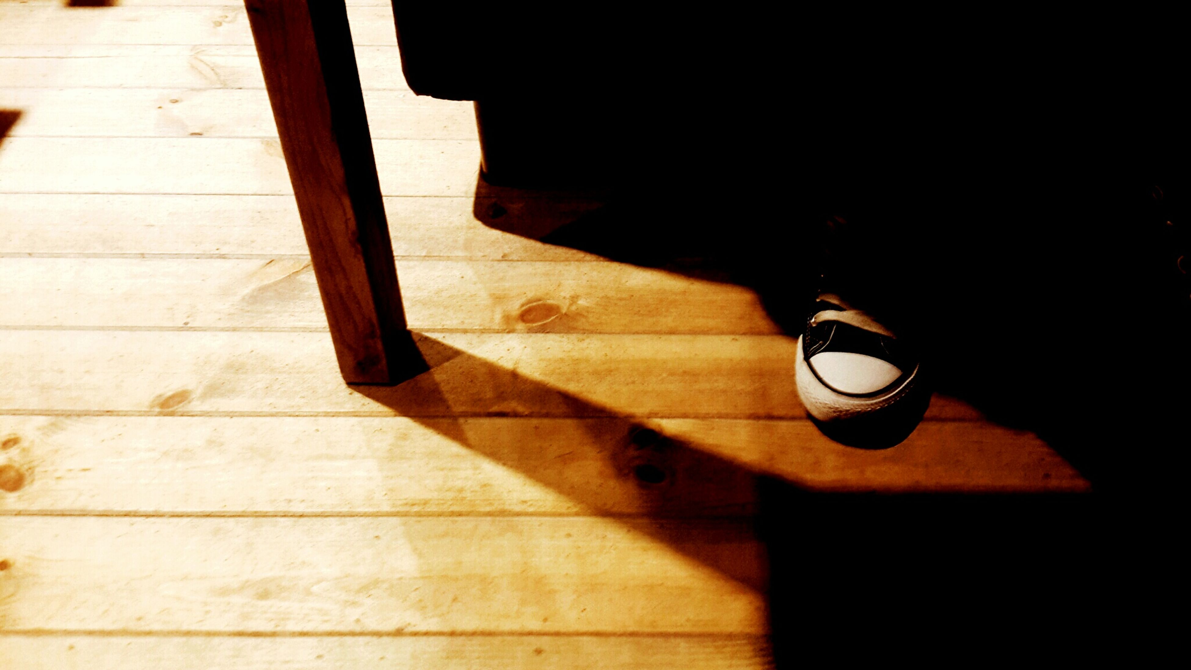 wood - material, indoors, high angle view, shadow, wooden, table, wood, flooring, hardwood floor, close-up, sunlight, no people, night, reflection, illuminated, black color, home interior, still life, floor