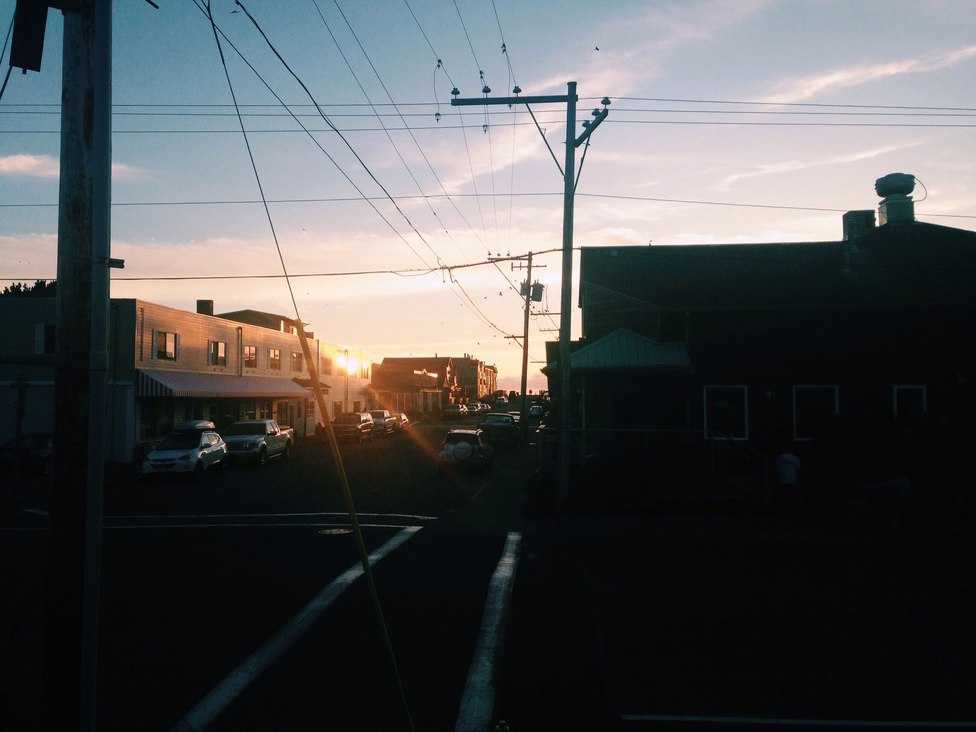 sunset, power line, electricity pylon, building exterior, transportation, sky, built structure, silhouette, architecture, cable, electricity, mode of transport, power supply, sun, street, car, power cable, sunlight, city, railroad track