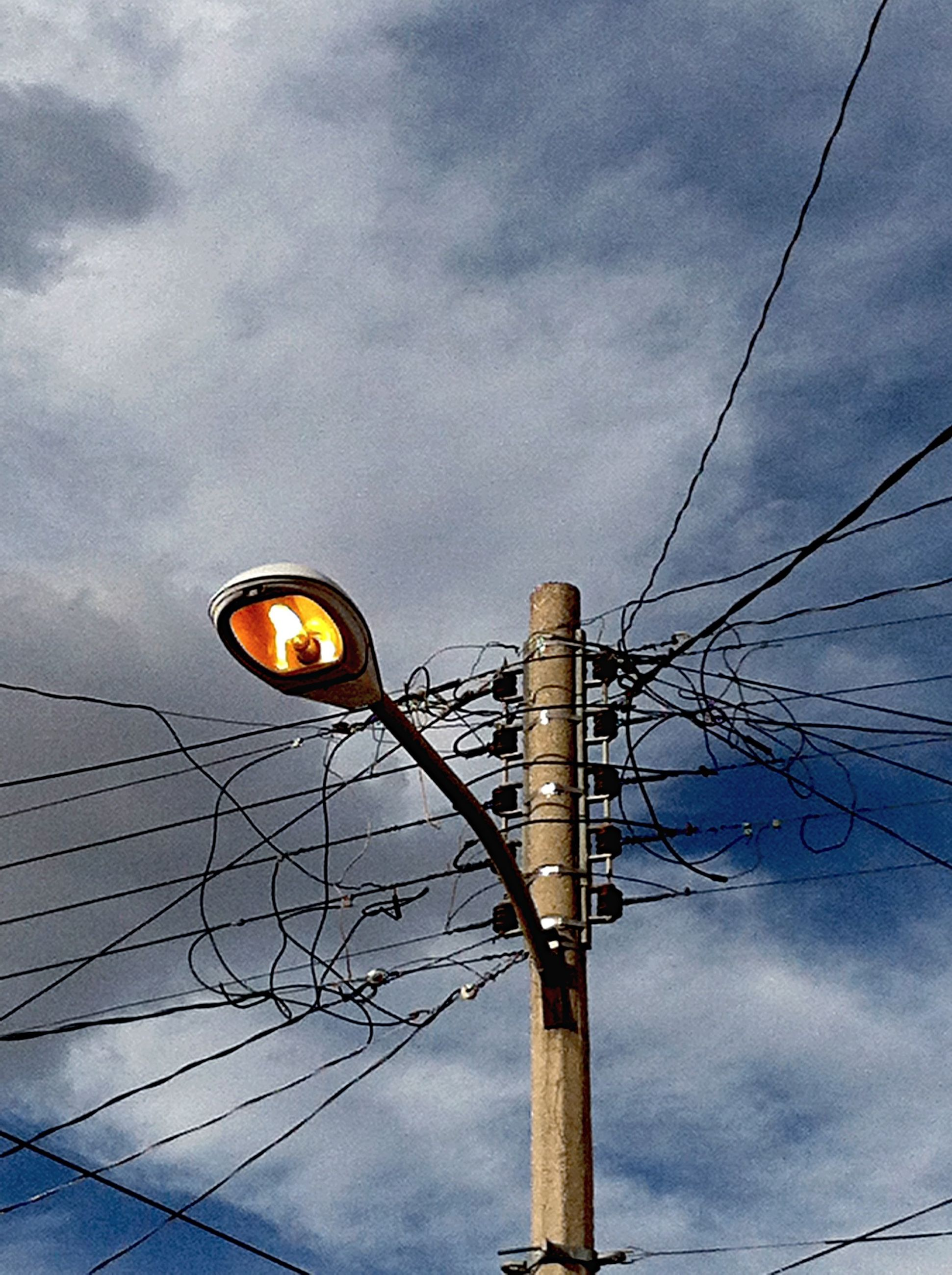 low angle view, electricity, power line, sky, connection, cable, power supply, electricity pylon, cloud - sky, lighting equipment, street light, cloudy, technology, fuel and power generation, power cable, cloud, built structure, no people, outdoors, dusk