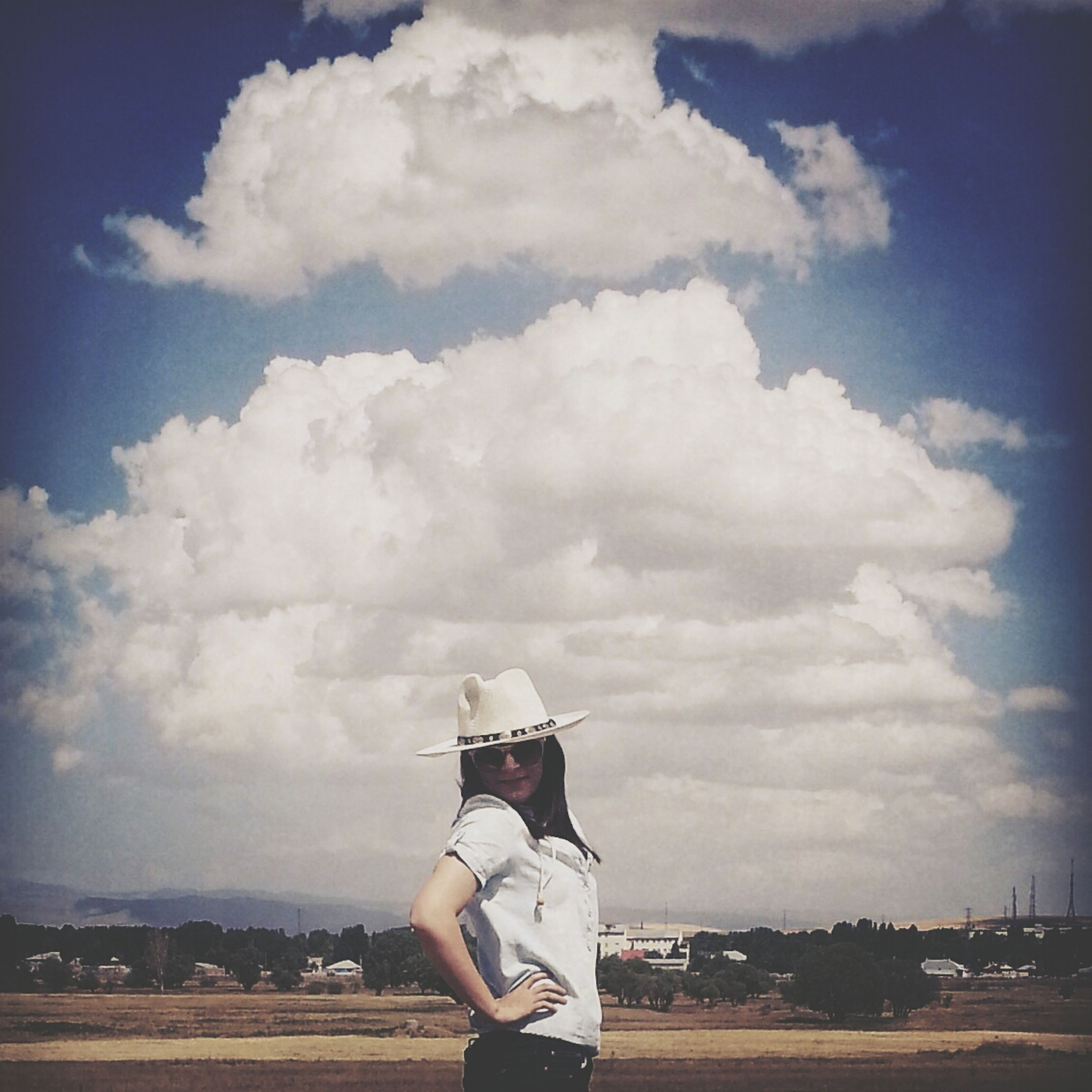 sky, cloud - sky, cloud, cloudy, leisure activity, day, lifestyles, landscape, rear view, casual clothing, outdoors, field, standing, building exterior, nature, built structure, full length, transportation