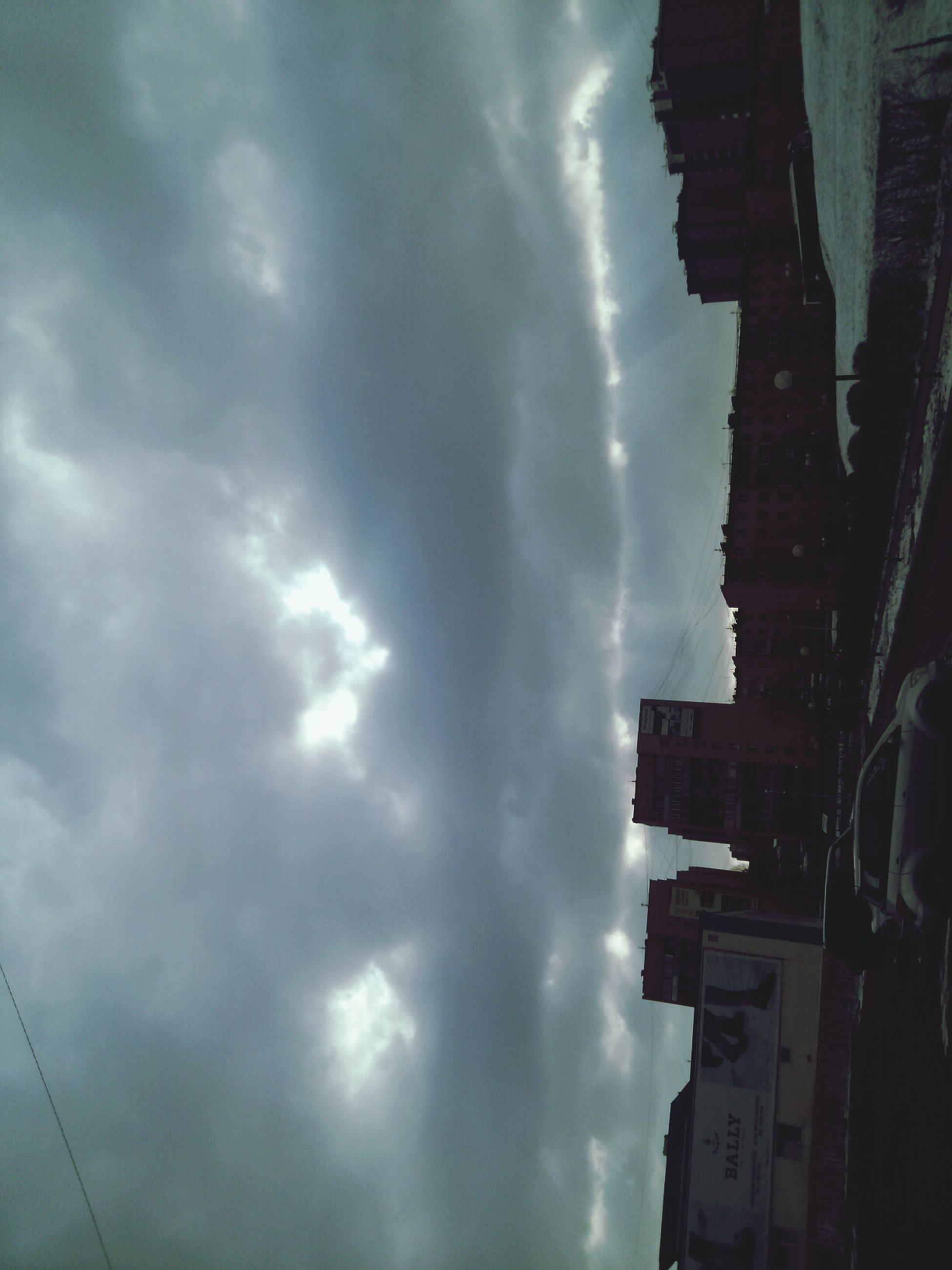 building exterior, architecture, built structure, sky, cloud - sky, cloudy, low angle view, city, building, cloud, weather, residential building, residential structure, overcast, dusk, outdoors, no people, silhouette, storm cloud, day