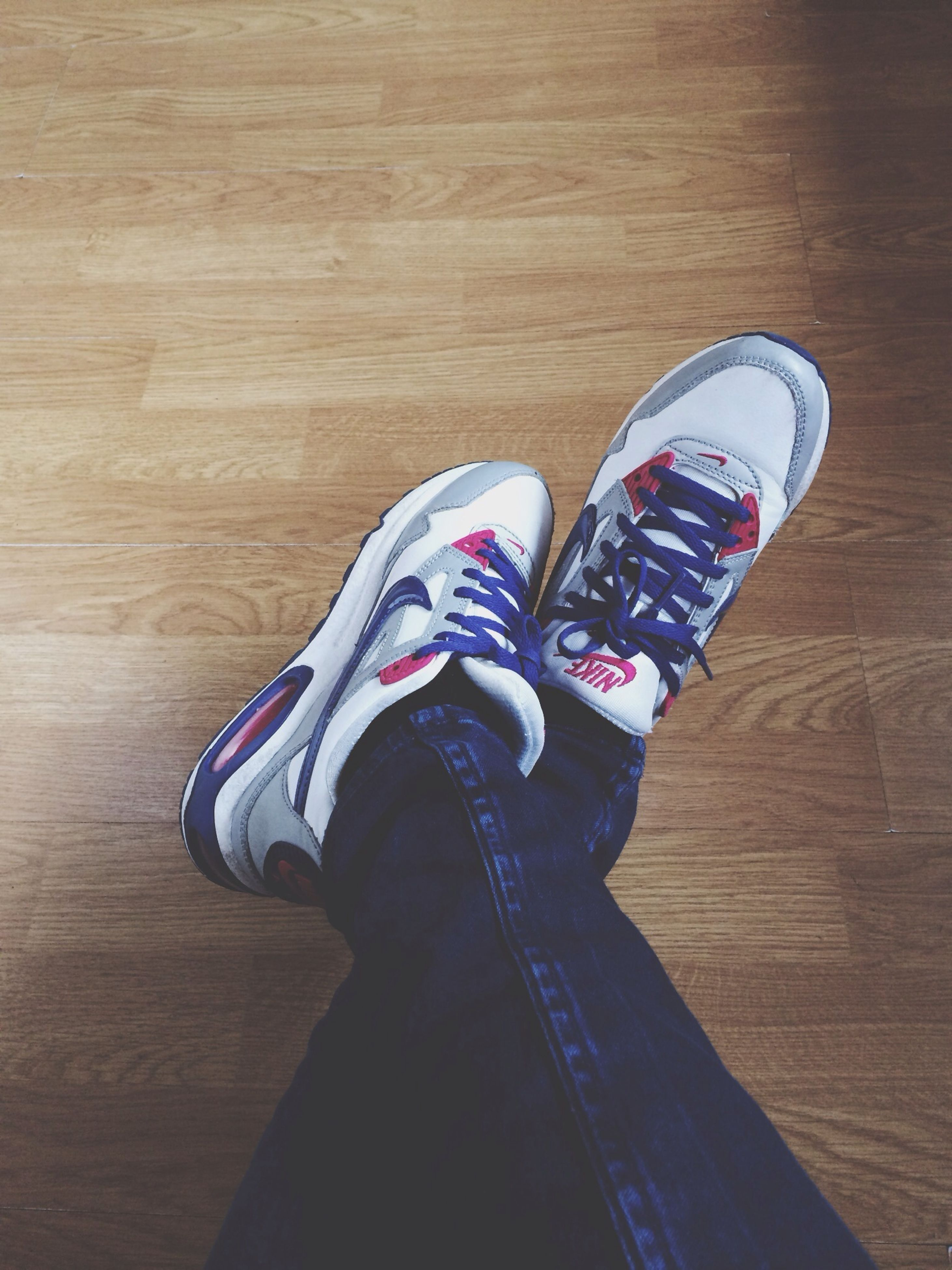 low section, shoe, person, footwear, personal perspective, jeans, high angle view, standing, human foot, lifestyles, flooring, indoors, hardwood floor, leisure activity, canvas shoe, men, casual clothing