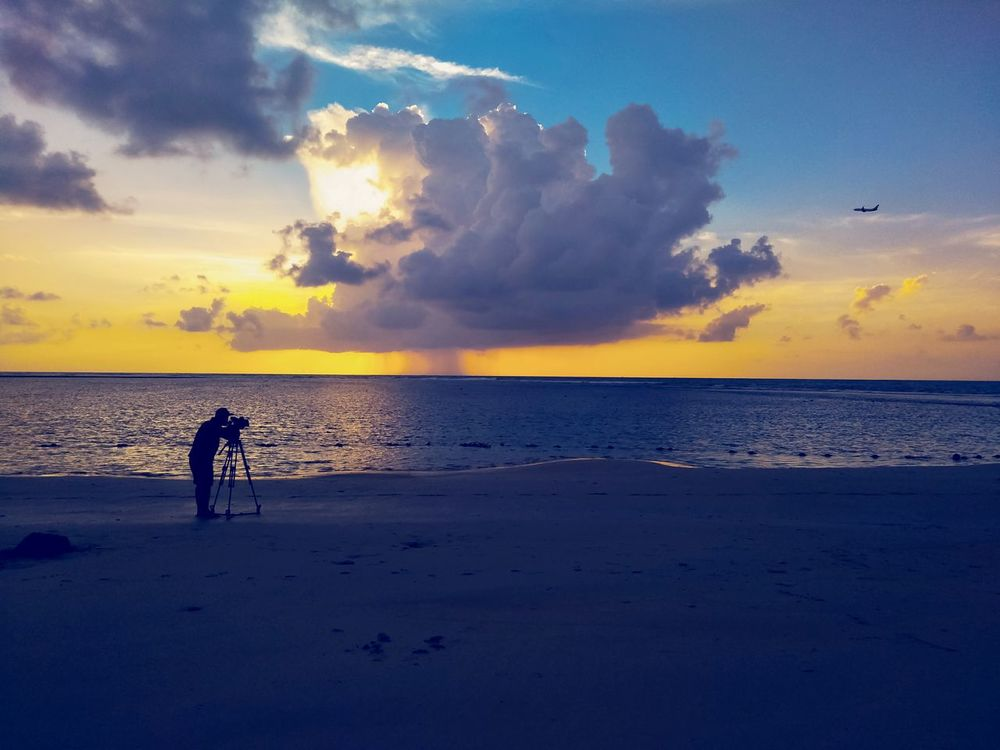 Photography is recording video of airplane flying on the sky during sunset time Lifestyles Togetherness Summer Boys Blue Childhood Nature Silhouette Outdoors Full Length Vacations Sea People Sunset Horizon Over Water Beach Sky Water Men Women Day Sand Real People Standing Sun