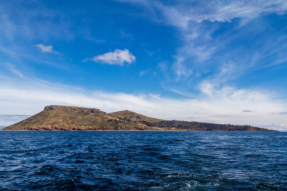 Photograph of the whole Amantani island from the point of view of a boat on the waters of Lake Titicaca, Puno, Peru. The sky and the water are blue and it is also possible to see clouds in the sky, trees and houses on the island and waves in the water. Adventure Amantaní Blue Calm Cloud Color Colorful Enjoy Hike House Inca Island Lake Landscape Mountain Peaceful Peru Puno Sky Titicaca Tranquility Travel Tree Water Wave