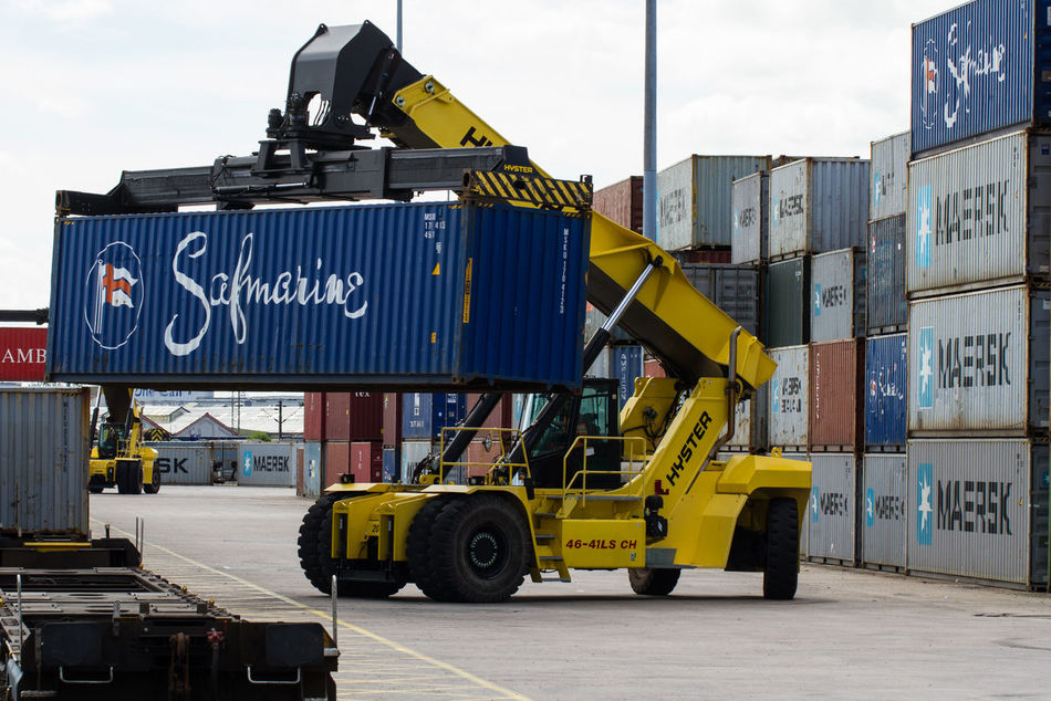 A heavy lifting machine lifts a cargo or shipping container into position in a busy goods yard. Boxes Business Cargo Commerce Containers Dock Docks Export Freight Heavy Import Industrial Industry Lifter Lifting Machine Machinery Movement Port Rail Sea Shipping  Stacker Stacking Trade