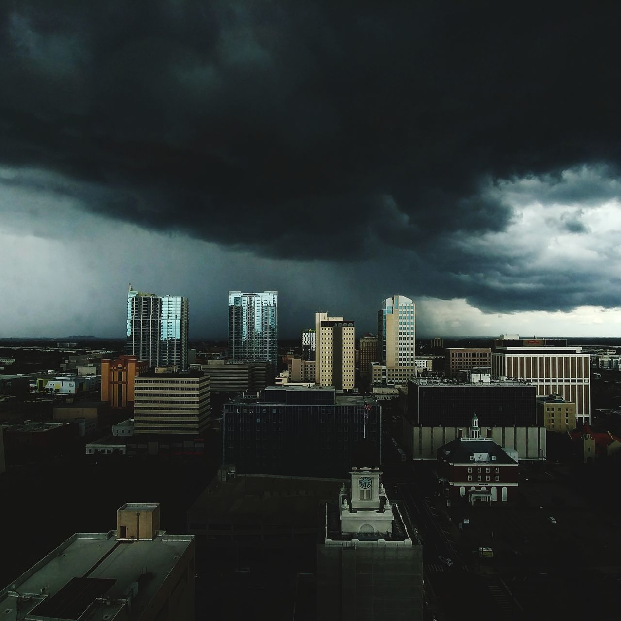 architecture, skyscraper, building exterior, cloud - sky, sky, city, cityscape, built structure, storm cloud, modern, outdoors, travel destinations, development, skyline, no people, building story, city life, tall, urban skyline, growth, day, illuminated
