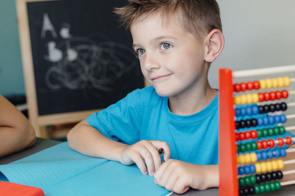 Smiling schoolboy working on math homework with an abacus Abacus Assignment Boy Caucasian Child Counting Critical Home Homeschooling Homework Independent  Kid Learn Learning Mathematics Maths Project Room School Schoolboy Schoolchild Solitary Student Thinking Young
