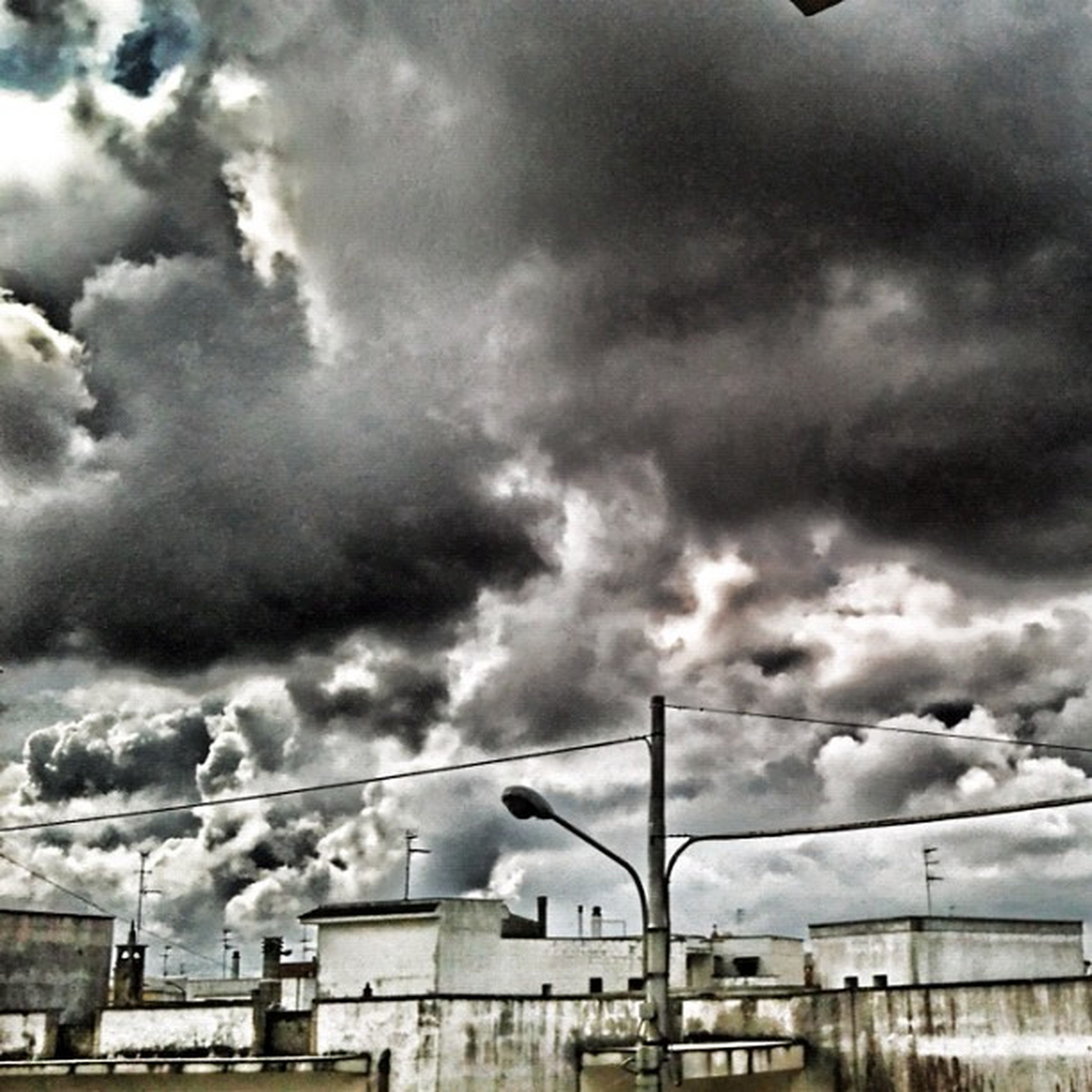 sky, cloud - sky, cloudy, architecture, low angle view, building exterior, built structure, weather, overcast, cloud, storm cloud, power line, cable, connection, outdoors, day, no people, building, cloudscape, industry