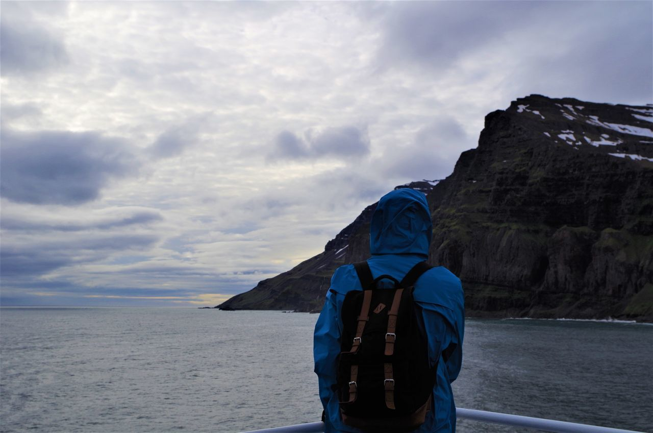 approaching iceland by ferry. Adult Adults Only Back Backpack Backview Blue Sky Cloud - Sky Day Ferry Ice Iceland Mountain Ocean One Person Outdoors People Raincoat Sea Seascape Seyðisfjörður Sightseeing Sky View Viewpoint Young Adult