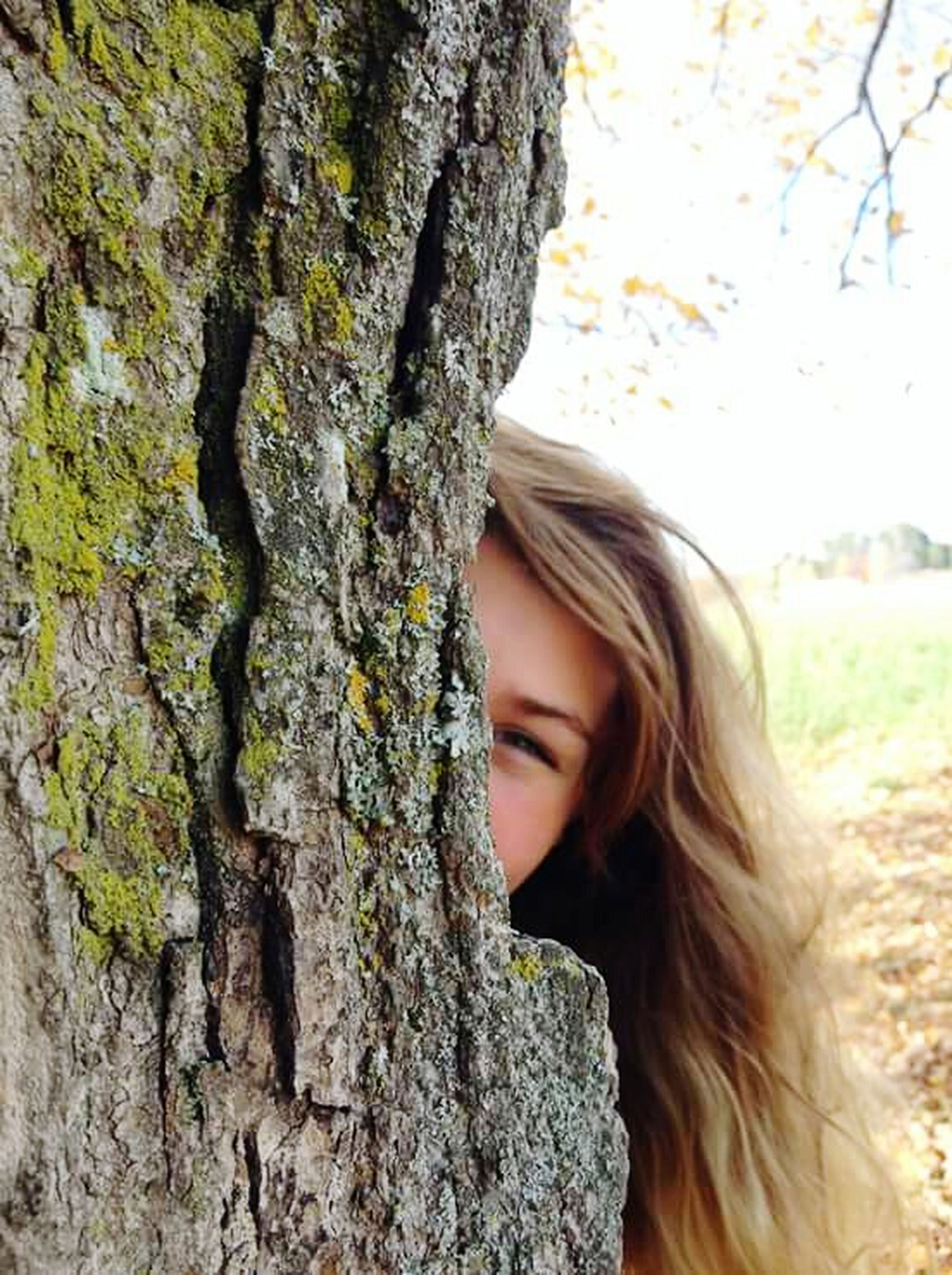 long hair, lifestyles, headshot, portrait, close-up, focus on foreground, leisure activity, beauty, tree trunk, day, outdoors, nature, casual clothing