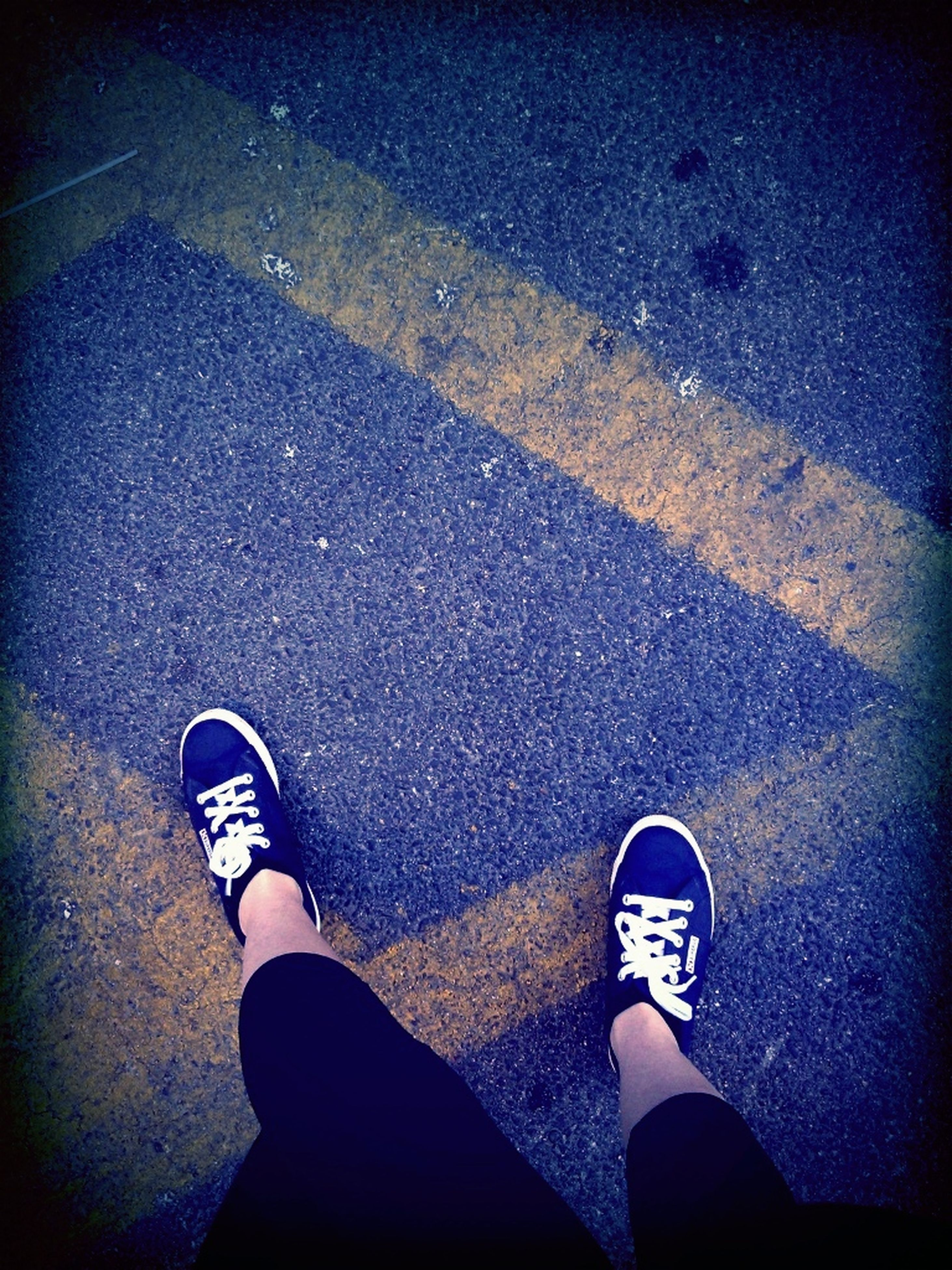 low section, person, shoe, personal perspective, standing, high angle view, lifestyles, street, human foot, footwear, men, leisure activity, road, directly above, asphalt, jeans, unrecognizable person