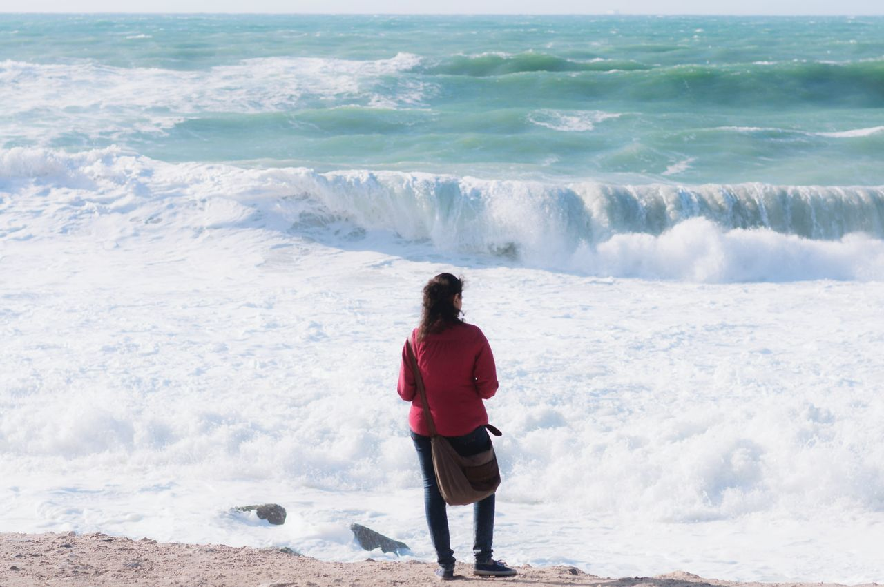 wave, surf, sea, real people, water, motion, nature, standing, beauty in nature, leisure activity, one person, rear view, shore, beach, power in nature, lifestyles, outdoors, day, scenics, ankle deep in water, women, full length, horizon over water, force, vacations, sky
