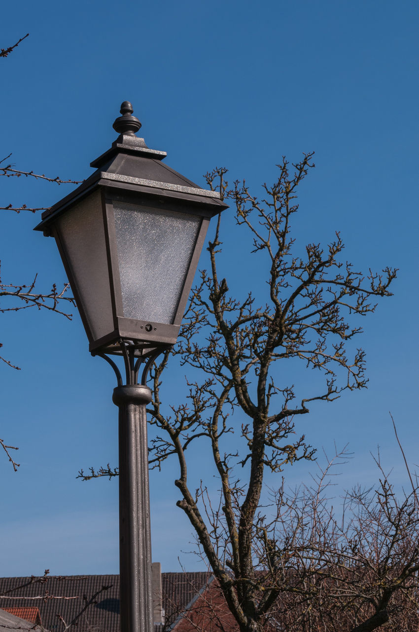 low angle view, lighting equipment, street light, outdoors, no people, tree, day, blue, clear sky, nature, sky, architecture
