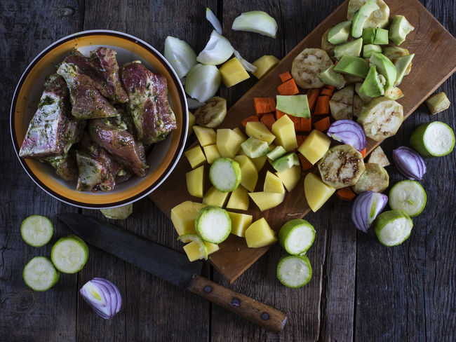 Marinated raw ribs and chopped vegetables on a cutting board on an old weathered wooden table Board Carrots Chopped Cutting Day Eggplant Food Freshness Green Olive Healthy Eating Knife Marinated No People Old Onions Potatoes Raw Ready-to-eat Ribs Table Vegetables Weathered Wooden Zucchini