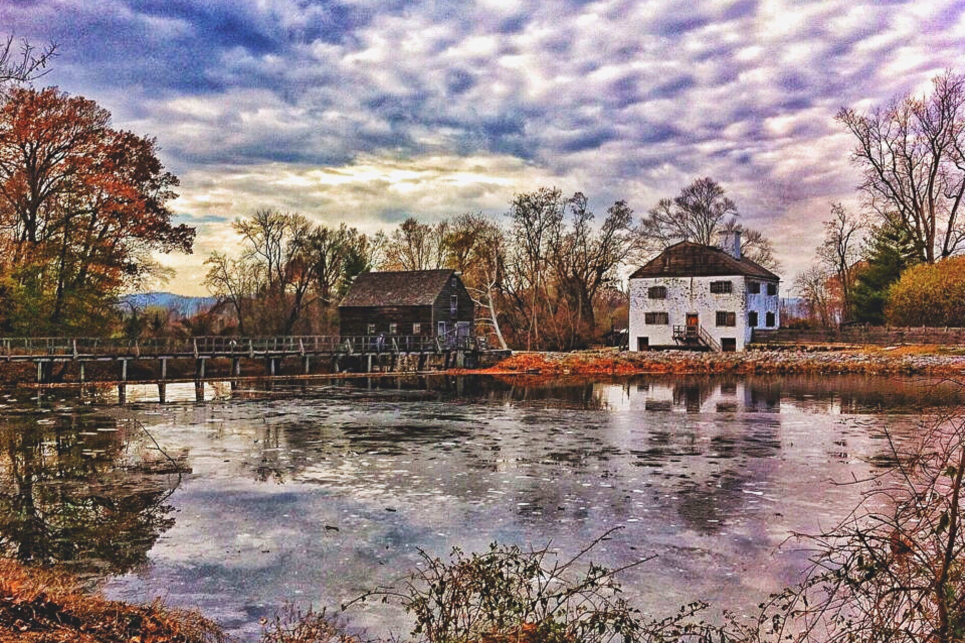 water, built structure, reflection, architecture, lake, tree, building exterior, waterfront, house, sky, tranquil scene, tranquility, cloud, calm, scenics, cloud - sky, cloudy, nature, day, outdoors, blue, beauty in nature, no people, riverbank