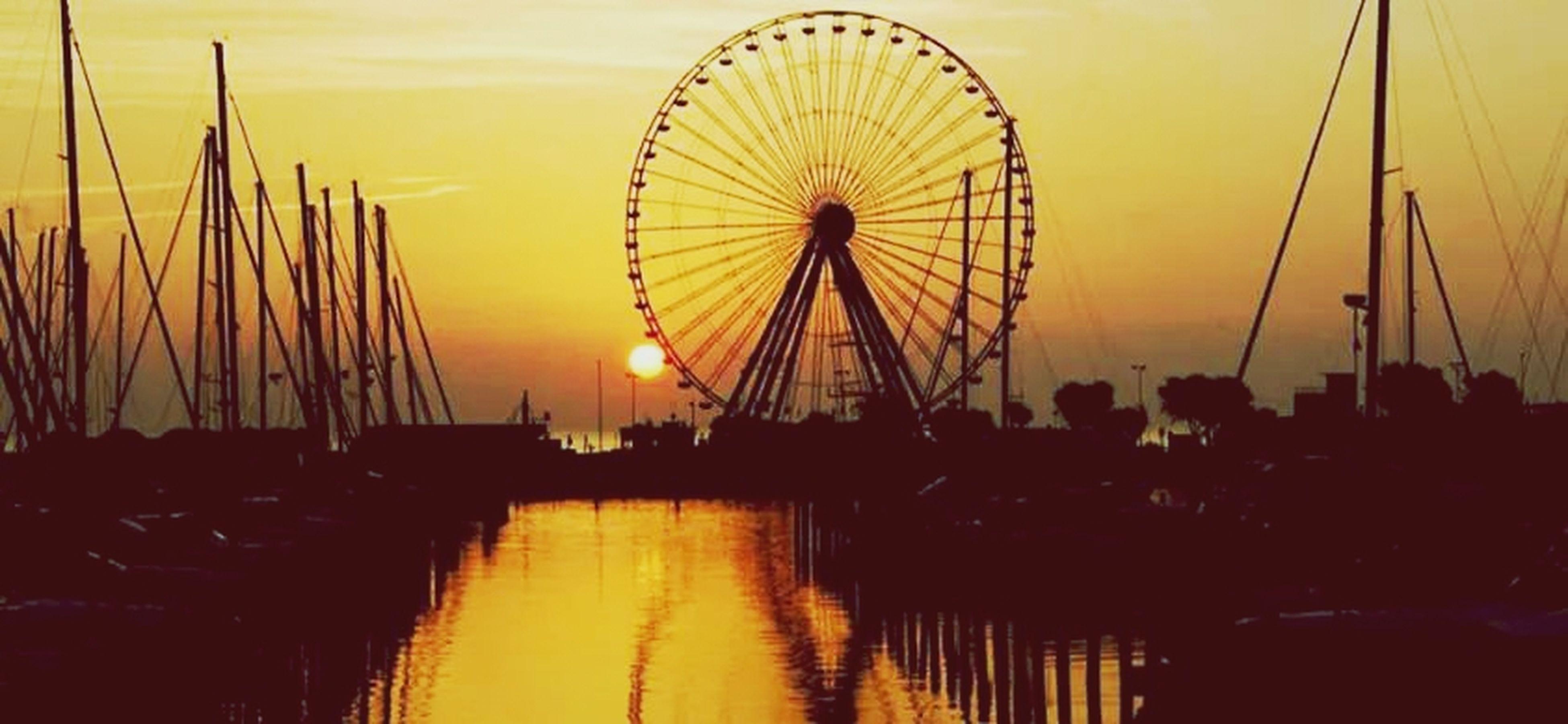 sunset, ferris wheel, amusement park, amusement park ride, arts culture and entertainment, silhouette, sky, orange color, water, nautical vessel, transportation, sea, mode of transport, boat, outdoors, nature, dusk, cloud - sky, mast, leisure activity
