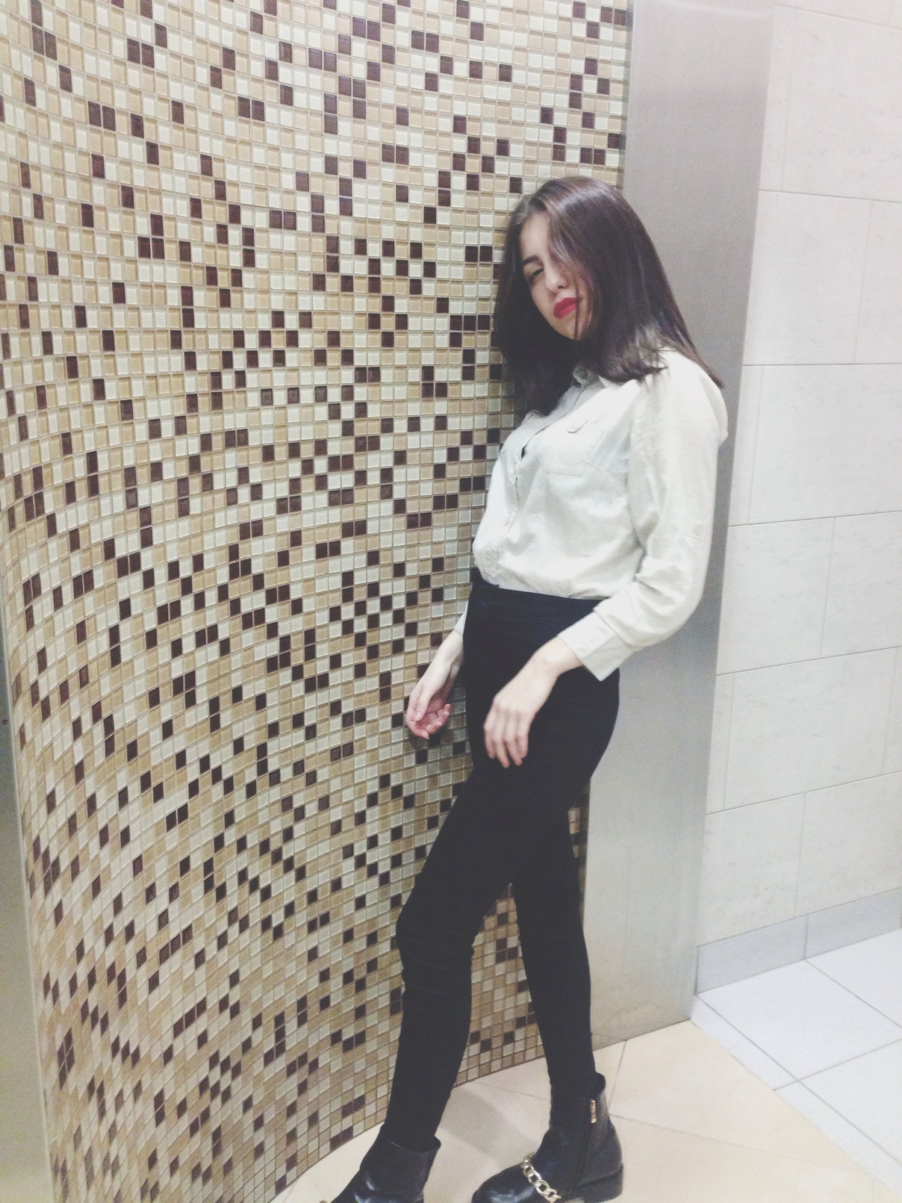 full length, casual clothing, lifestyles, young adult, standing, person, front view, leisure activity, young women, architecture, built structure, building exterior, three quarter length, portrait, looking at camera, wall - building feature, walking, hands in pockets