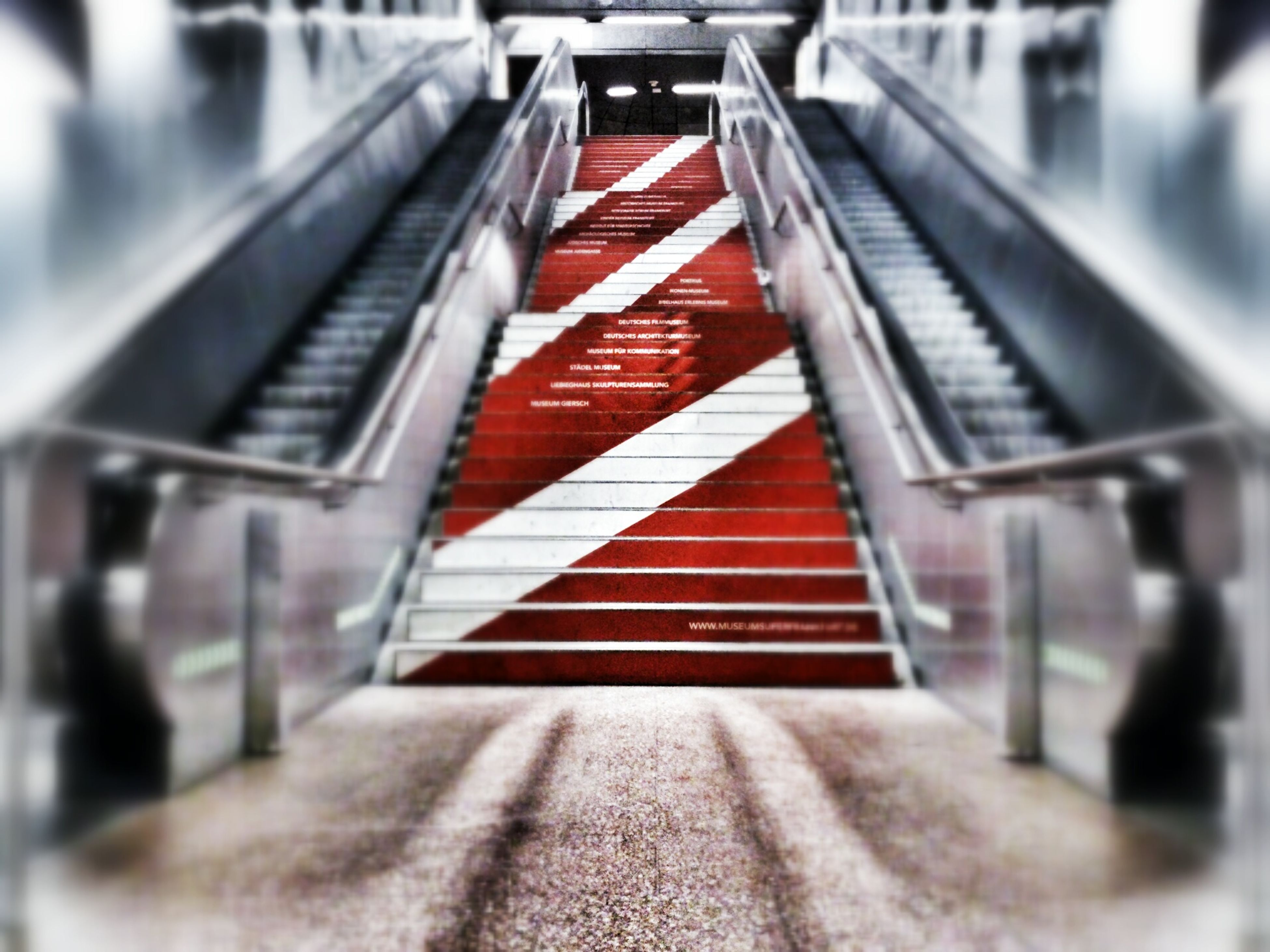 steps, railing, staircase, built structure, architecture, red, steps and staircases, low angle view, building exterior, selective focus, day, metal, focus on foreground, no people, outdoors, stairs, diminishing perspective, connection, sunlight, striped