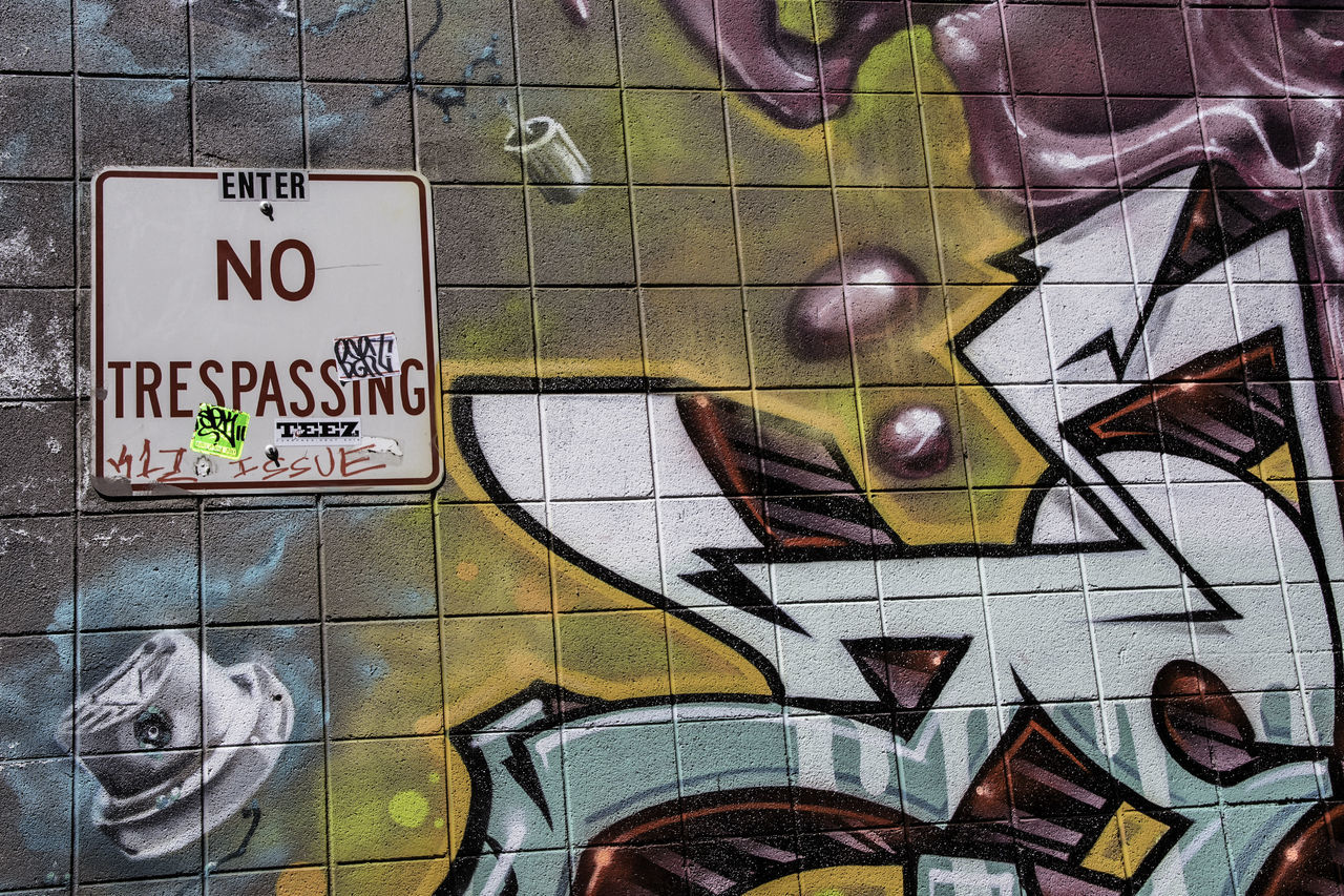No trespassing sign with stickers and written comments next to graffiti in an alley. Alley Building Exterior Communication Flouting The Rules No People No Trespassing Sign Resist Rules Sign Street Art Streetphotography Text