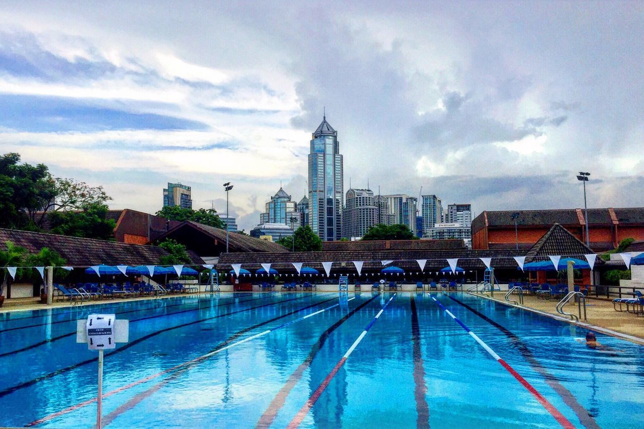swimming pool, water, architecture, built structure, building exterior, cloud - sky, sky, tower, swimming lane marker, day, large group of people, outdoors, real people, travel destinations, city, skyscraper, modern, people