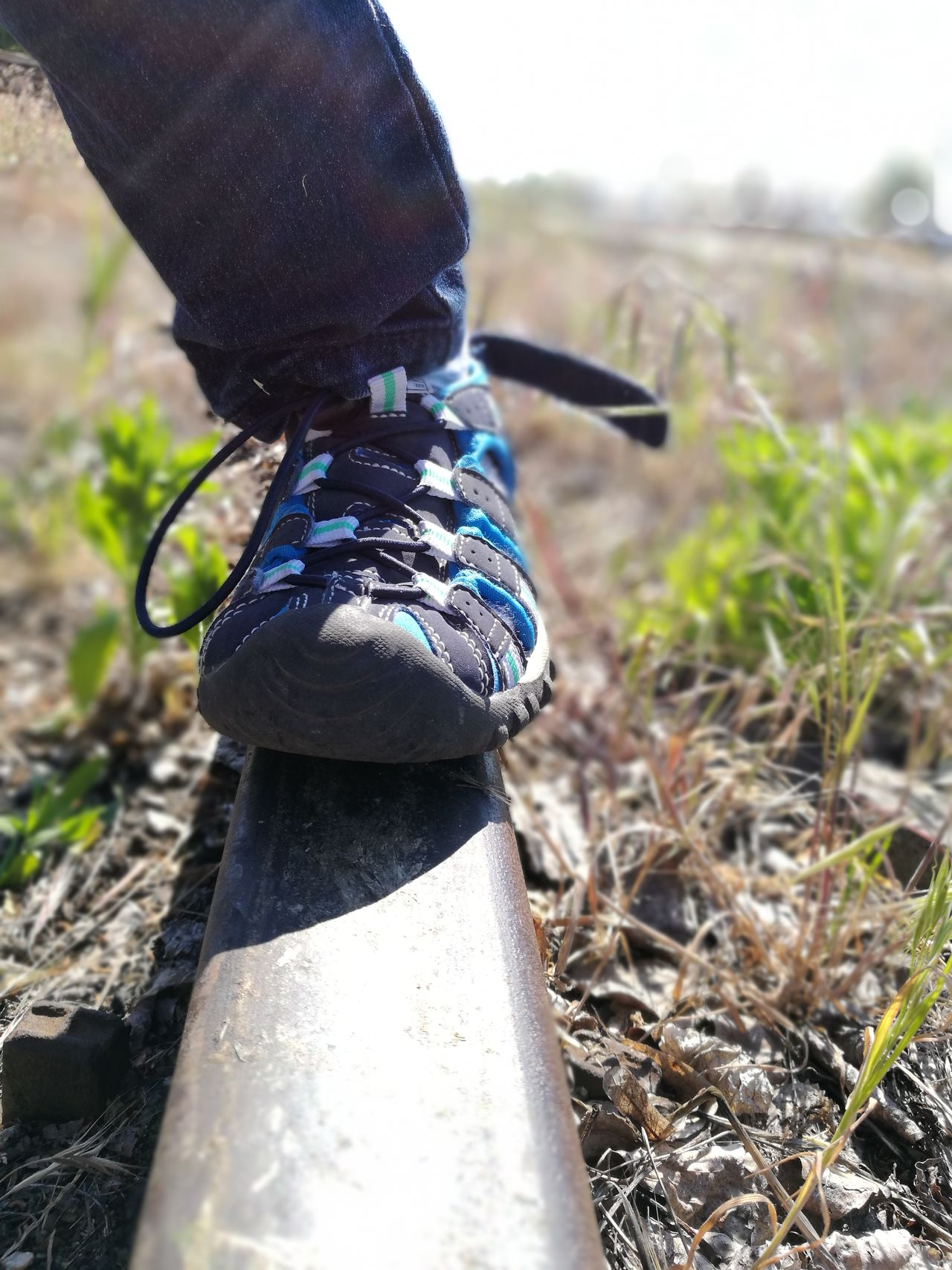 Focus On Foreground Day Outdoors No People Close-up Grass Rail Train LINE Weedy Young Adult Out Of Order Standing Summer Low Section Human Body Part Cropped Body The Purist (no Edit, No Filter) Shoe Hiking Sandal Childhood The Great Outdoors - 2017 EyeEm Awards Out Of The Box Let's Go. Together.