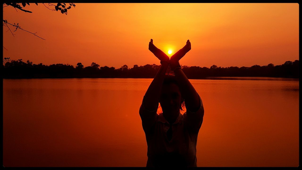 sunset, silhouette, orange color, nature, beauty in nature, real people, sky, sun, lake, tranquil scene, leisure activity, scenics, one person, outdoors, tree, lifestyles, water, human hand, one animal, standing, animals in the wild, women, clear sky, mammal, day, people