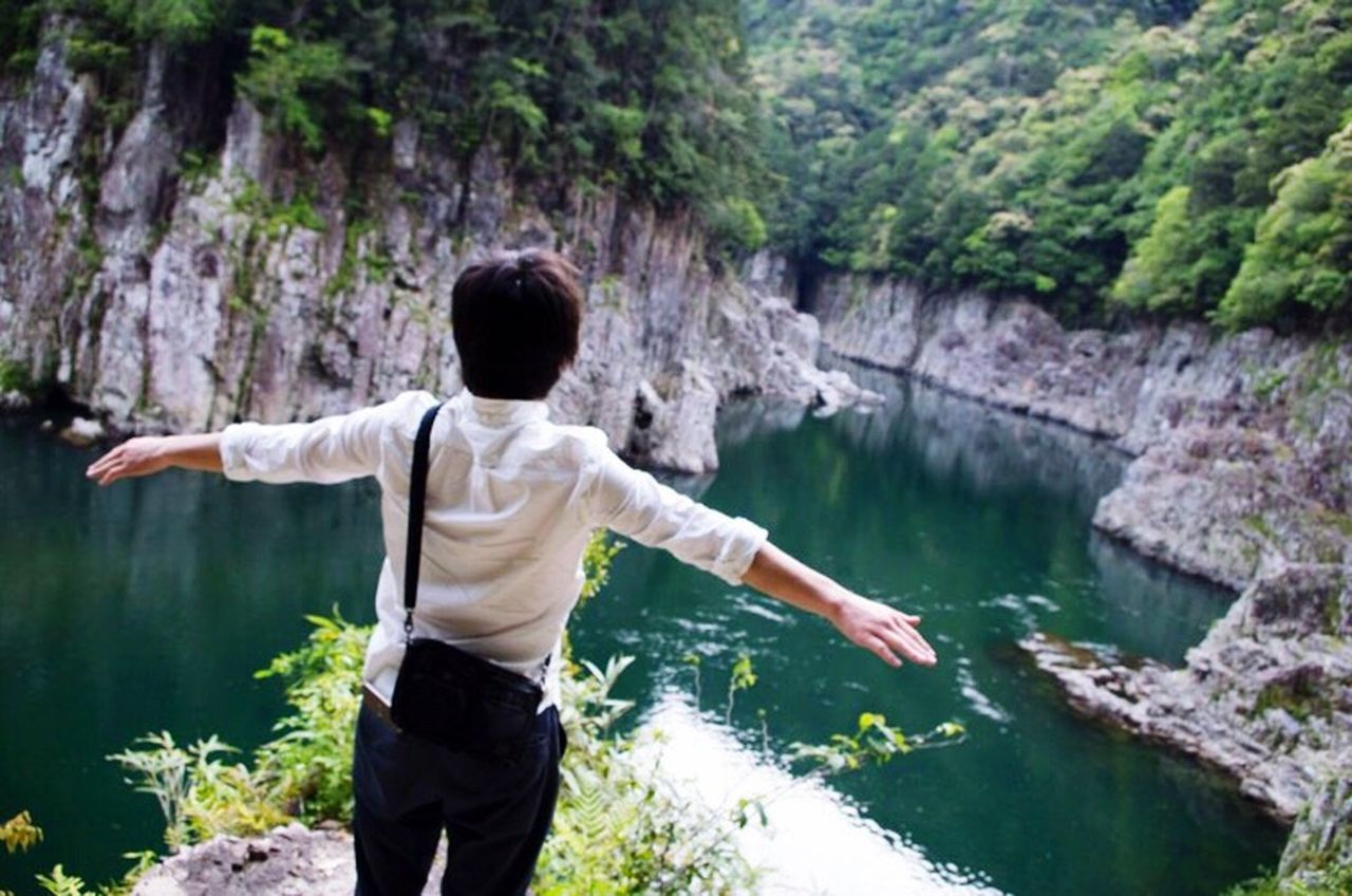rear view, water, one person, nature, casual clothing, lake, rock - object, outdoors, one man only, people, day, exploration, standing, discovery, forest, adventure, beauty in nature, waterfall, childhood, tree, adult, human body part, child, only men, young adult