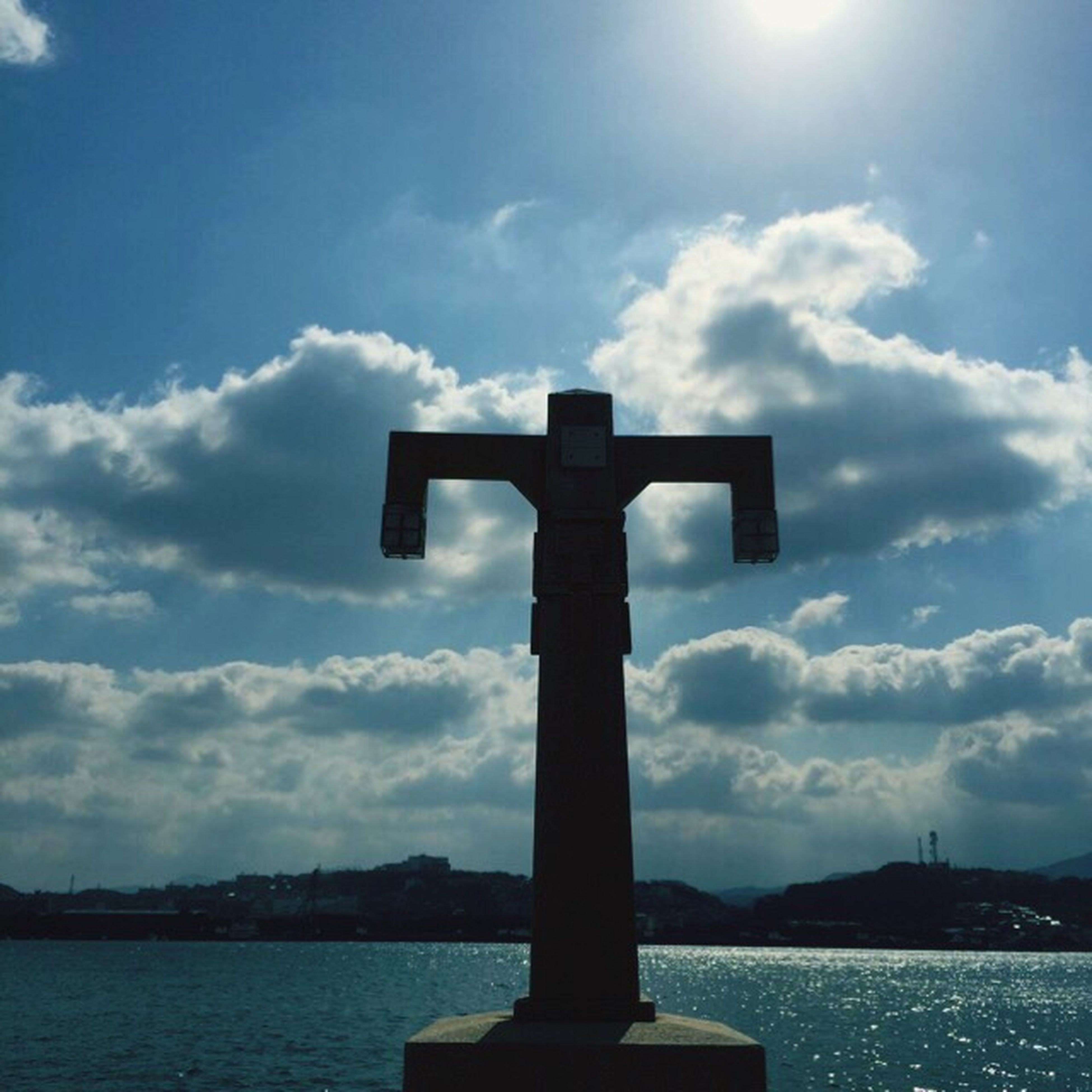 sky, human representation, water, religion, cross, cloud - sky, spirituality, silhouette, sculpture, statue, cloud, no people, guidance, art and craft, outdoors, art, low angle view