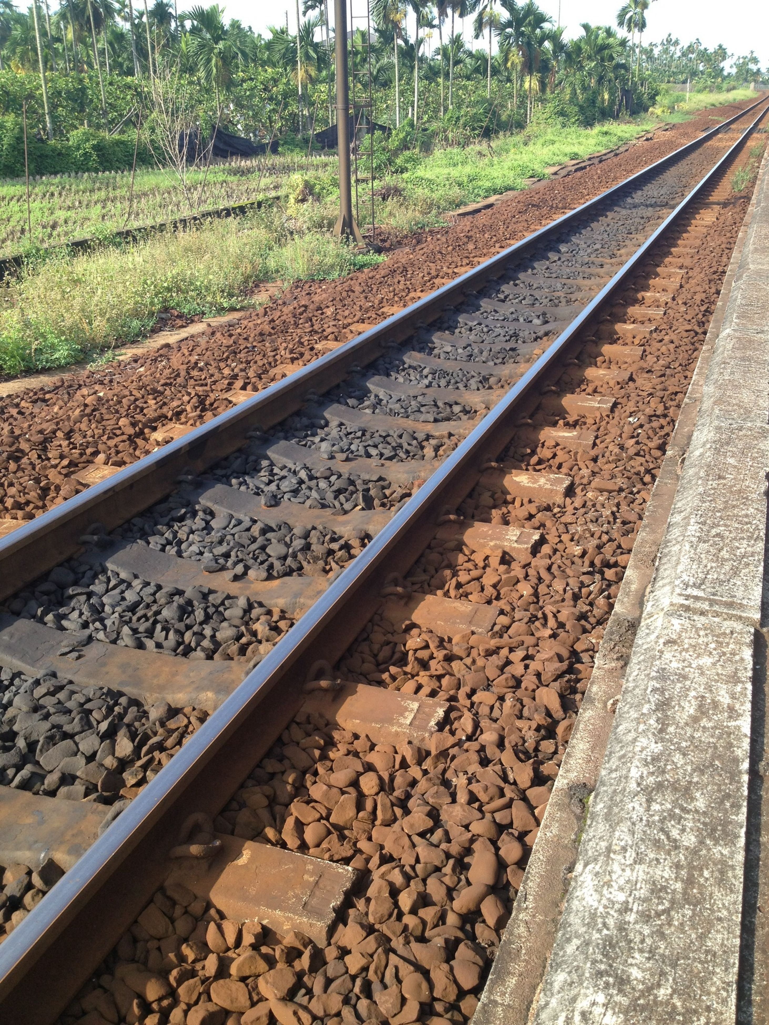 railroad track, rail transportation, transportation, diminishing perspective, public transportation, the way forward, railway track, vanishing point, high angle view, metal, day, stone - object, gravel, straight, tree, travel, no people, outdoors, long, railroad station