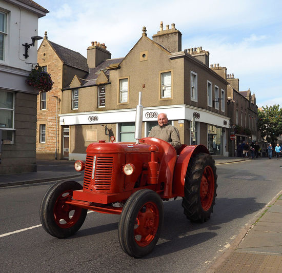 Kirkwall - Orkney Islands, Scotland Architecture People Real People Men Sky Red Day Outdoors Transportation Scottish Highlands Remote Location Antique Tractor Cloud - Sky Building Exterior Built Structure Orkney Islands A Taste Of Scotland Bleak And Cold High Street Kirkwall Man On Tractor Tractor On Public Road