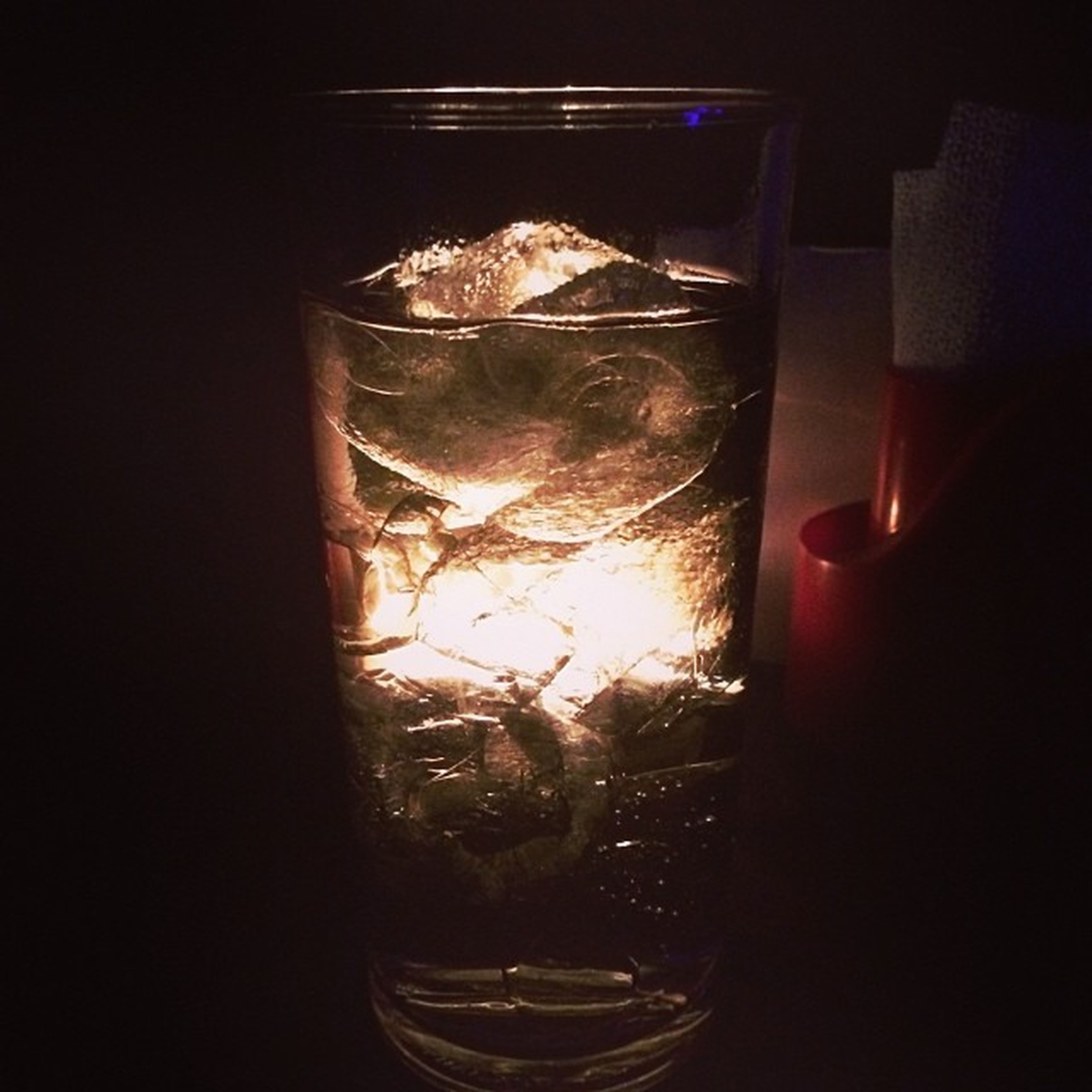 indoors, glass - material, transparent, window, dark, reflection, close-up, darkroom, glass, glowing, illuminated, water, no people, copy space, burning, night, light - natural phenomenon, drinking glass, black background, home interior